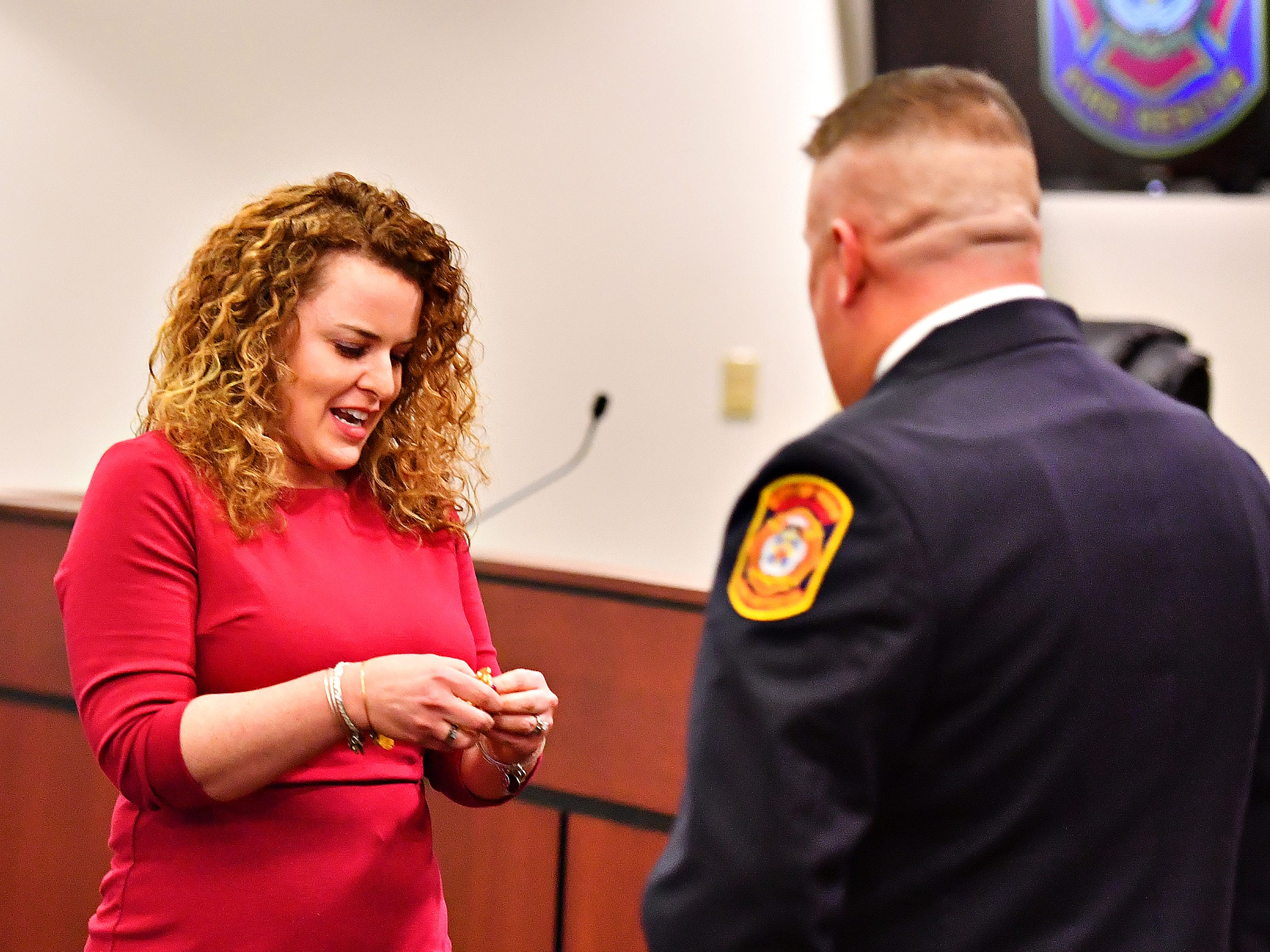 Jess Deardorff, left, prepares to pin her husband, York City Fire Chief Chad Deardorff during his swearing-in ceremony at York City Hall in York City, Friday, March 8, 2019. Dawn J. Sagert photo