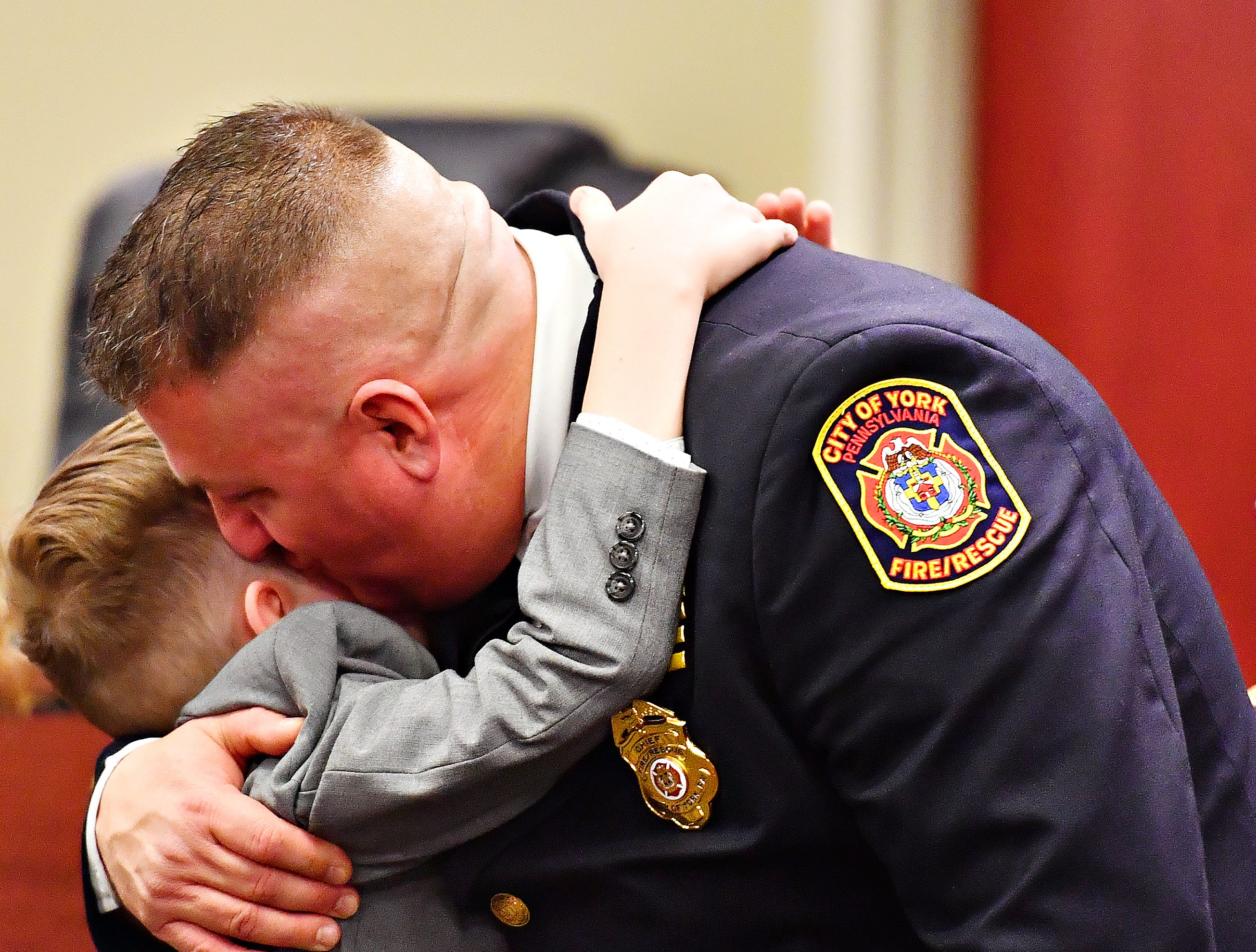 York City Fire Chief Chad Deardorff is embraced by his son, Adam, 9, during the new chief's swearing-in ceremony at York City Hall in York City, Friday, March 8, 2019. Dawn J. Sagert photo