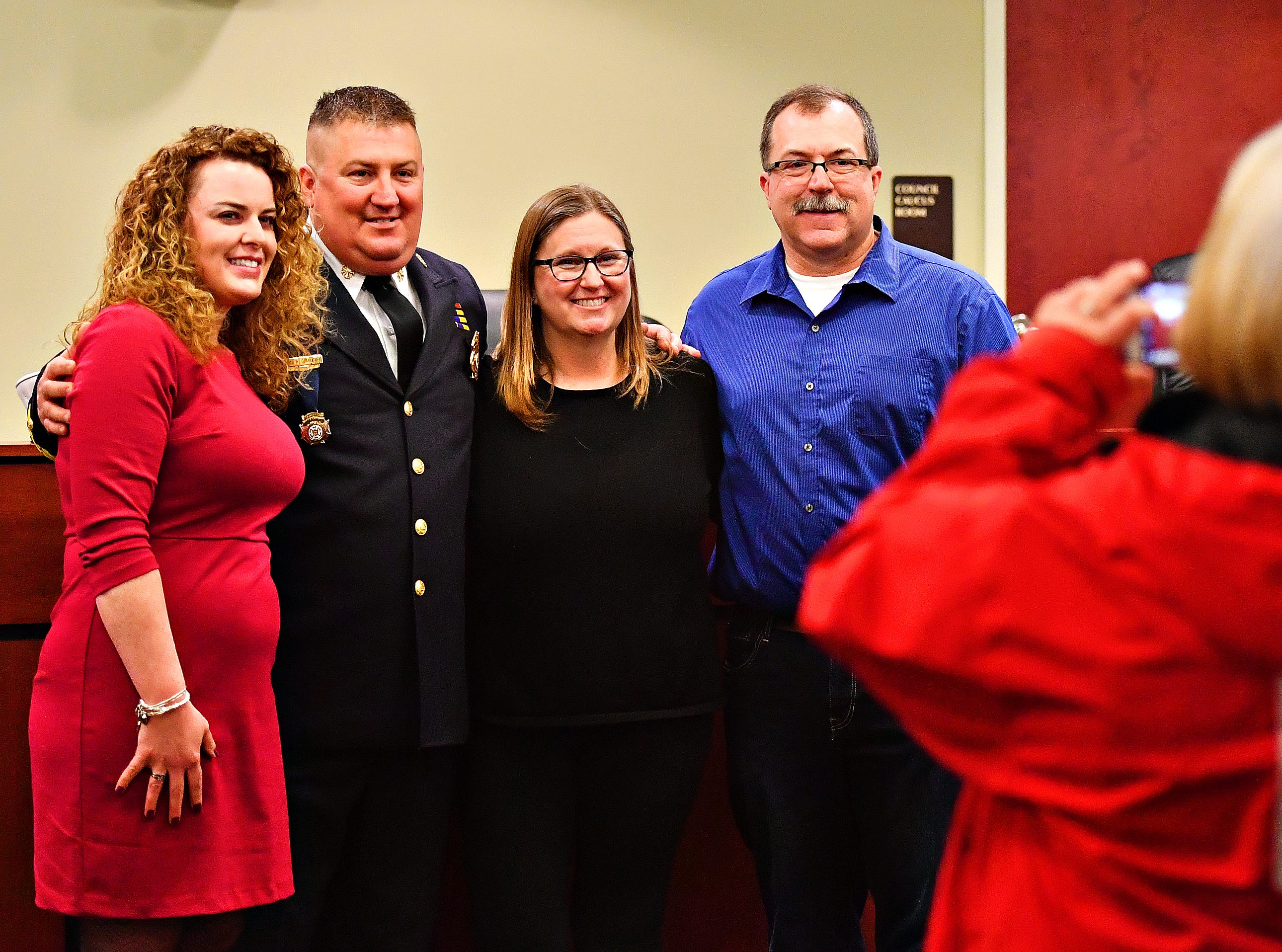 From left, Jess Deardorff, newly sworn in York City Fire Chief Chad Deardorff, Barb Michaels and retired York City Fire Chief David Michaels pose for a photo following Deardorff's swearing-in ceremony at York City Hall in York City, Friday, March 8, 2019. Dawn J. Sagert photo