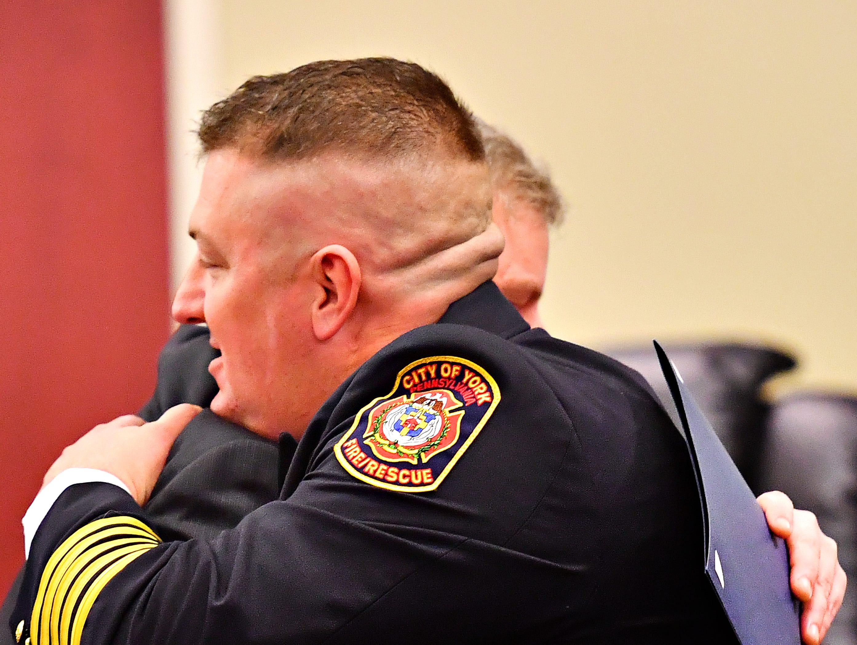 York City Mayor Michael Helfrich hugs York City Fire Chief Chad Deardorff during a swearing-in ceremony at York City Hall in York City, Friday, March 8, 2019. Dawn J. Sagert photo
