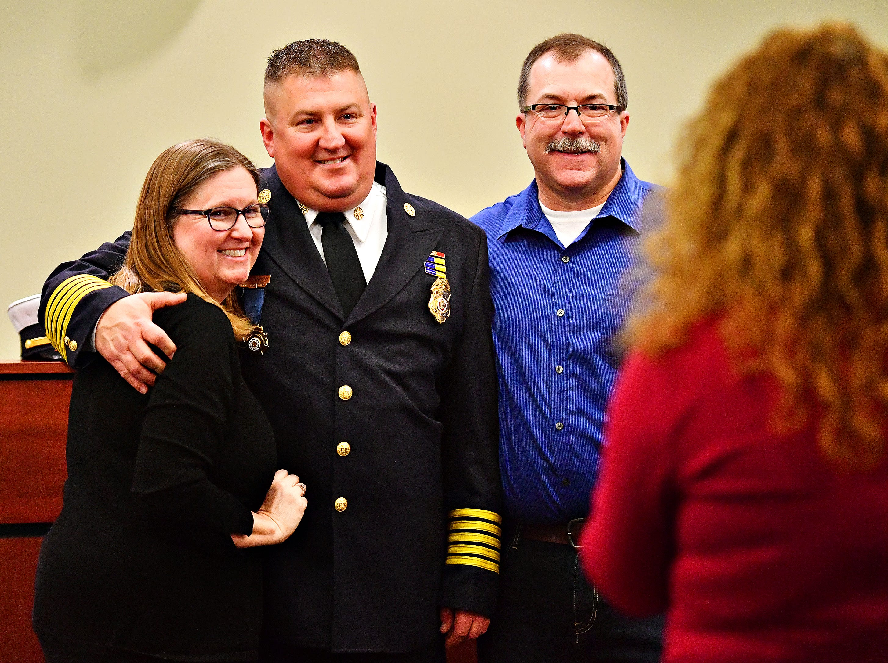 Barb Michaels, left, and former York City Fire Chief David Michaels, right, flank newly sworn in York City Fire Chief Chad Deardorff while Deardorff's wife Jess takes a photo following the new chief's swearing-in ceremony at York City Hall in York City, Friday, March 8, 2019. Dawn J. Sagert photo