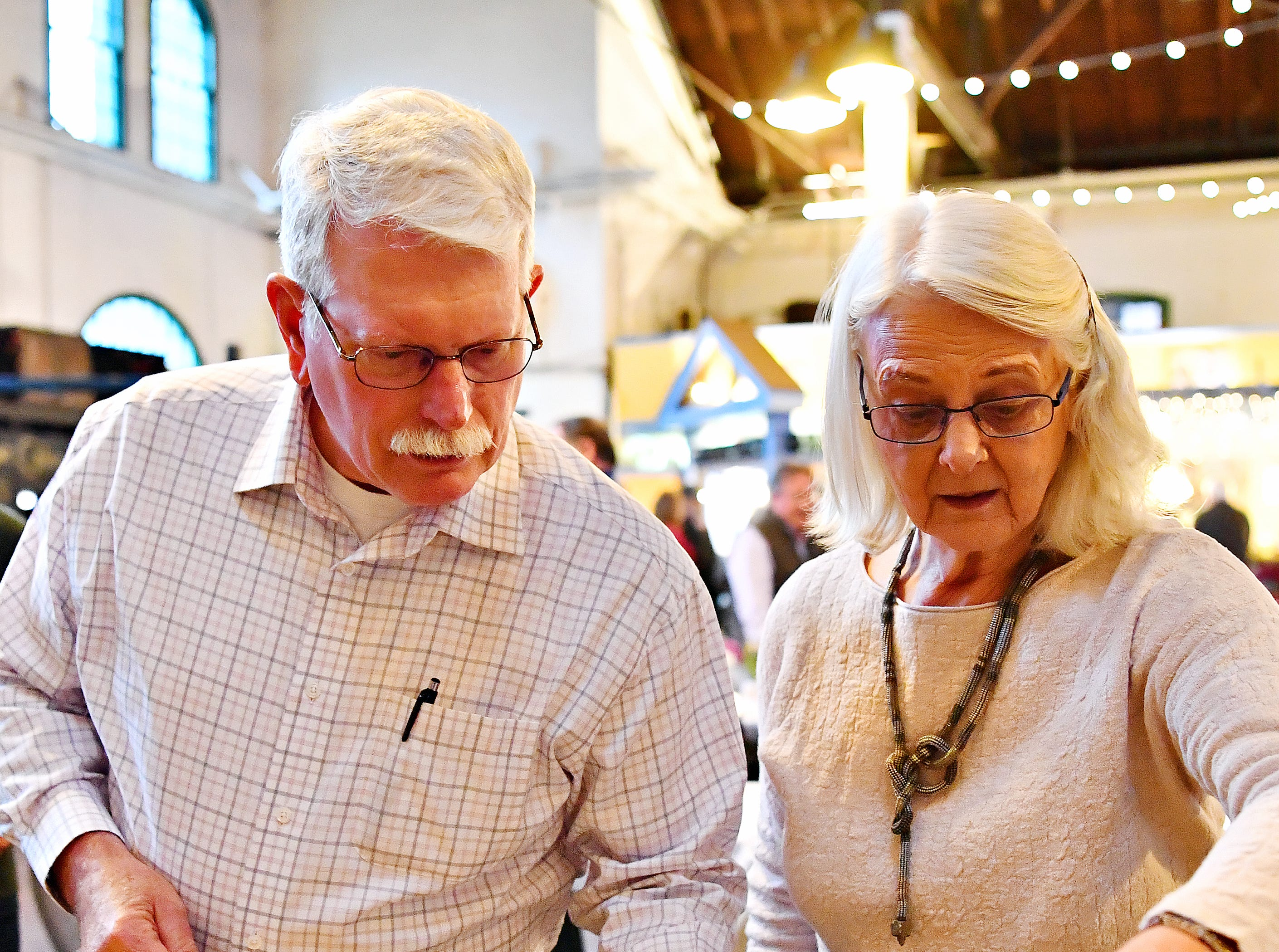 Beekeepers Frank Bodenberg, left, of Gettysburg, and Lauren Andersen, of Stewartstown, examine honey products being tasted during the York County Beekeepers' Association Centennial Banquet at Central Market in York City, Friday, March 8, 2019. Bodenberg has been keeping bees for about eight years, and Andersen six. Dawn J. Sagert photo