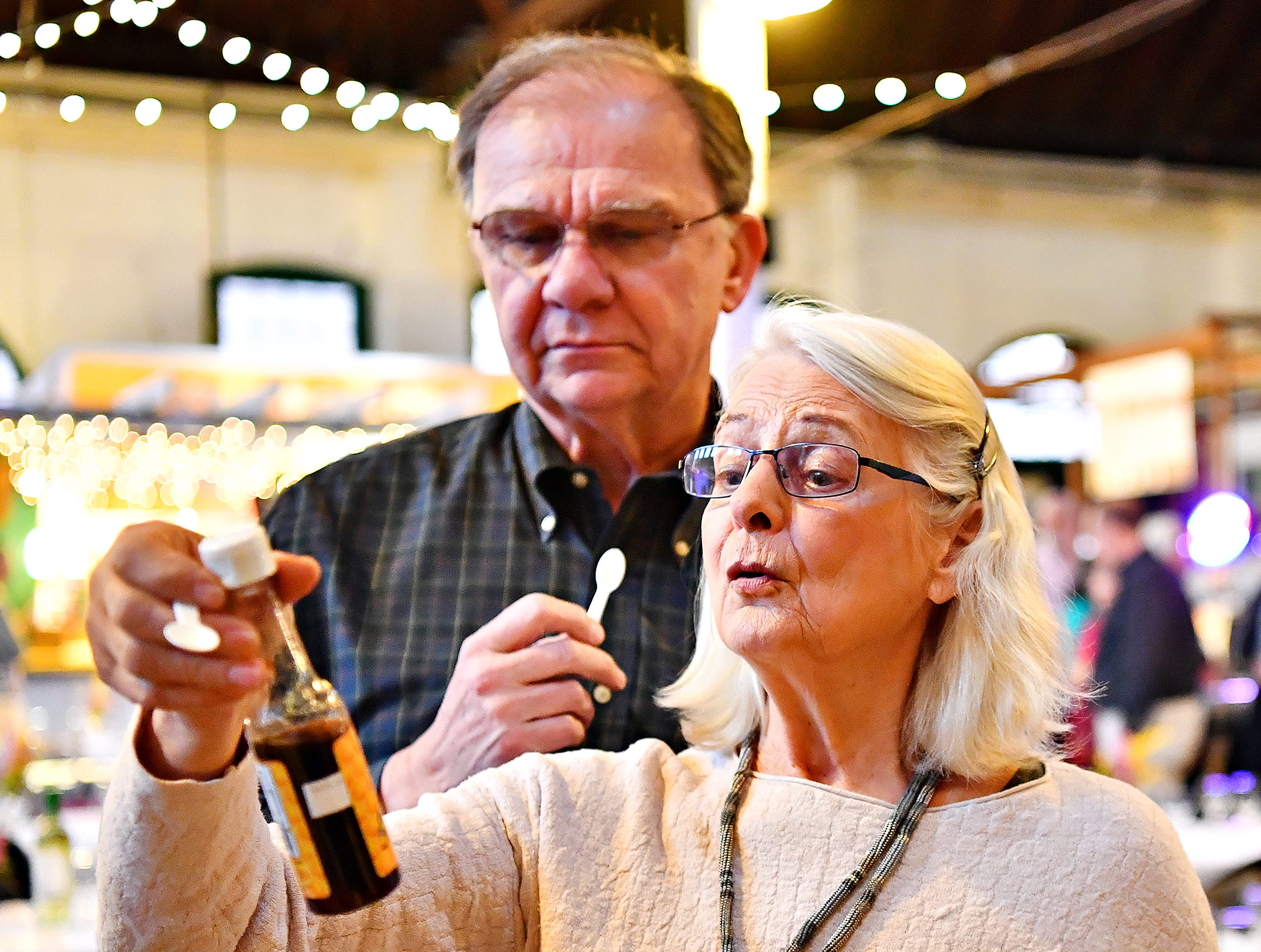 Ron Schultz, left, of Baltimore, looks on as Lauren Andersen, of Stewartstown, examines one of the honey products being tasted during the York County Beekeepers' Association Centennial Banquet at Central Market in York City, Friday, March 8, 2019. Andersen has been keeping bees for about six years and has eight colonies. Dawn J. Sagert photo