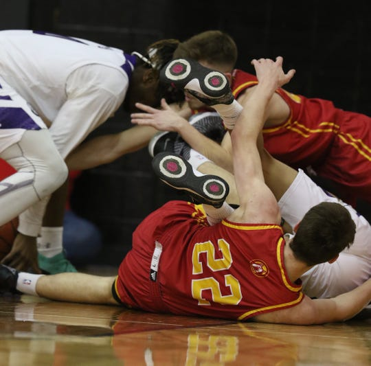 Greece Odyssey 's Aric Williams tries to get a hold of the ball while Olean's Josh Bihler reaches through his leg for it.  Tangled on the floor are Olean's Matt Droney and Greece Odyssey's Travon Harper.