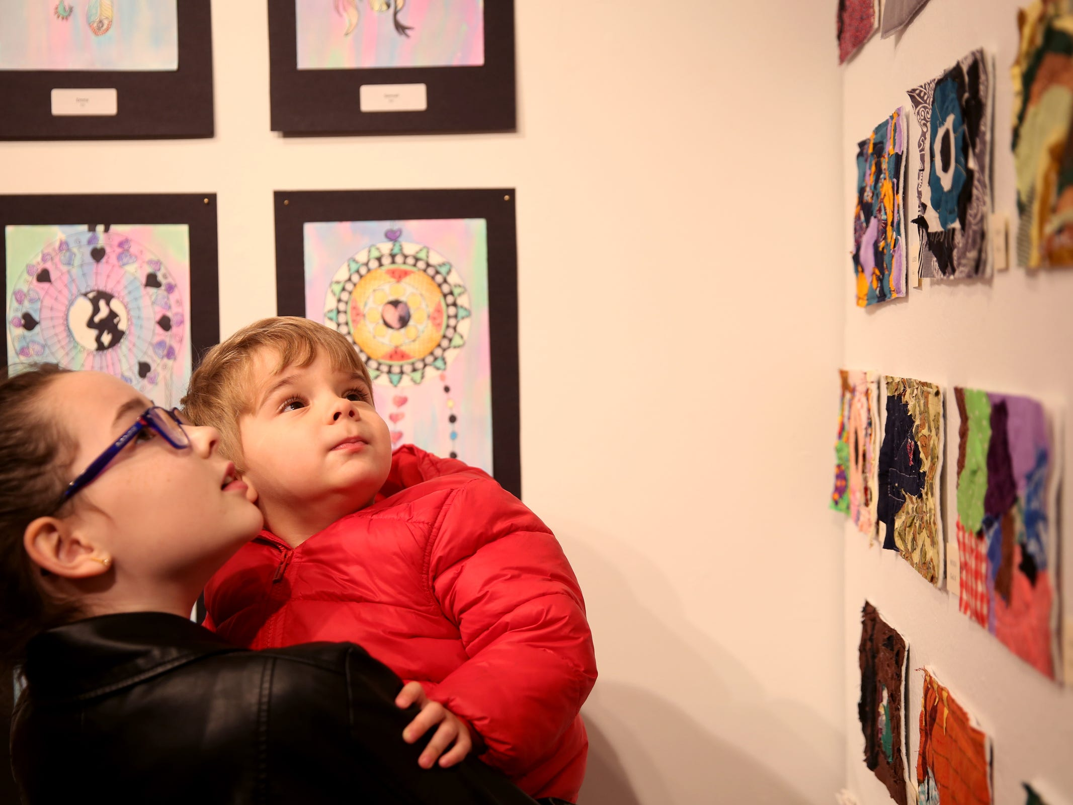 Lauren Burwash, a Zena Springs Farm School fourth-grader, holds Henry Sparks, 2, while looking at art during the awards reception for the 10th annual Young Artists' Showcase at the Bush Barn Art Center in Salem on March 9, 2019. The exhibit features artwork by more than 400 students in Marion, Polk and Yamhill counties and runs through April 20.