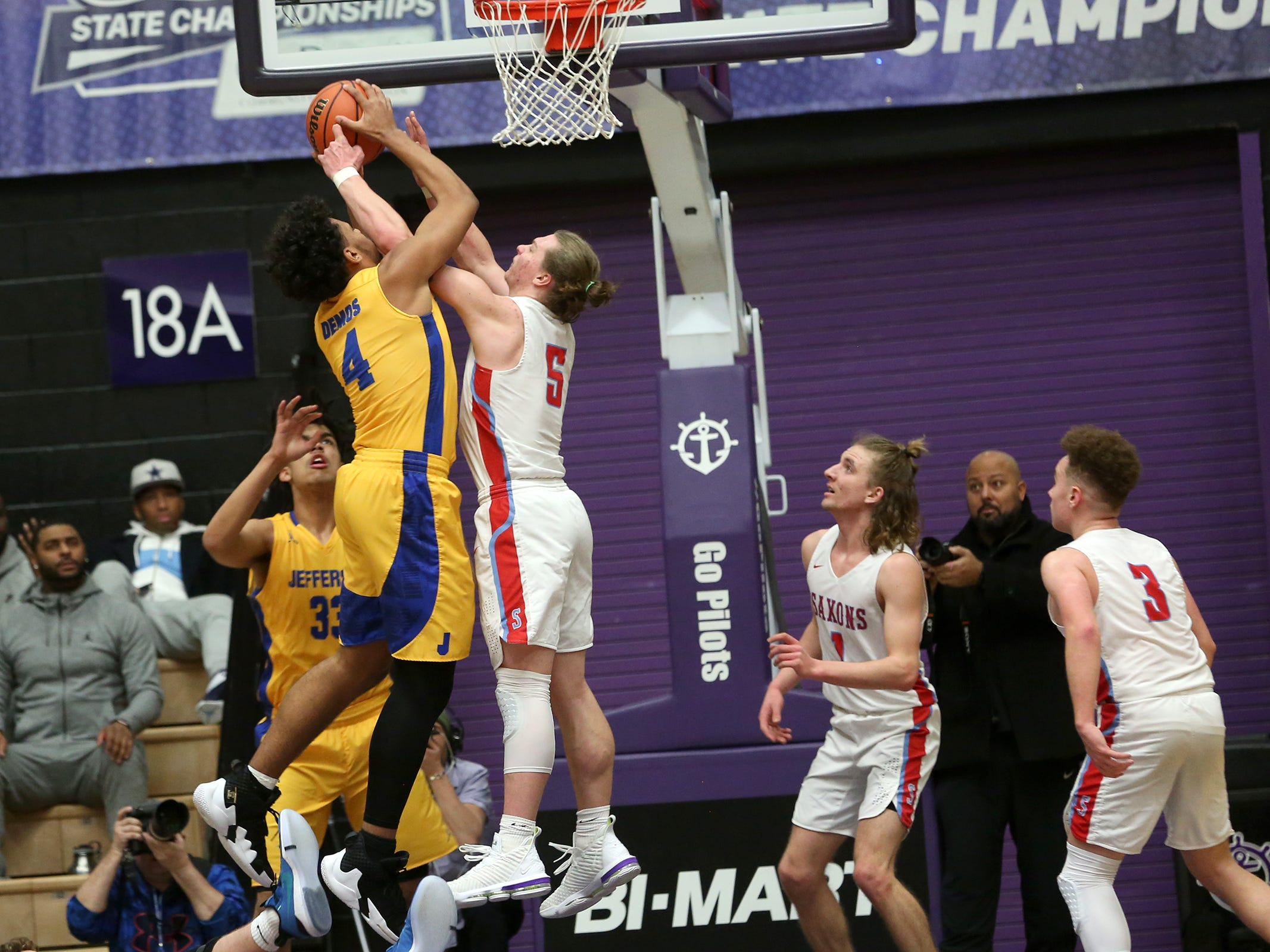 South Salem's Ryan Brown (5) and Jefferson's Nate Rawlins-Kibonge (4) struggle for the ball during the South Salem vs. Jefferson boys basketball OSAA 6A semifinal game at Chiles Center in Portland on Friday, March 8, 2019.