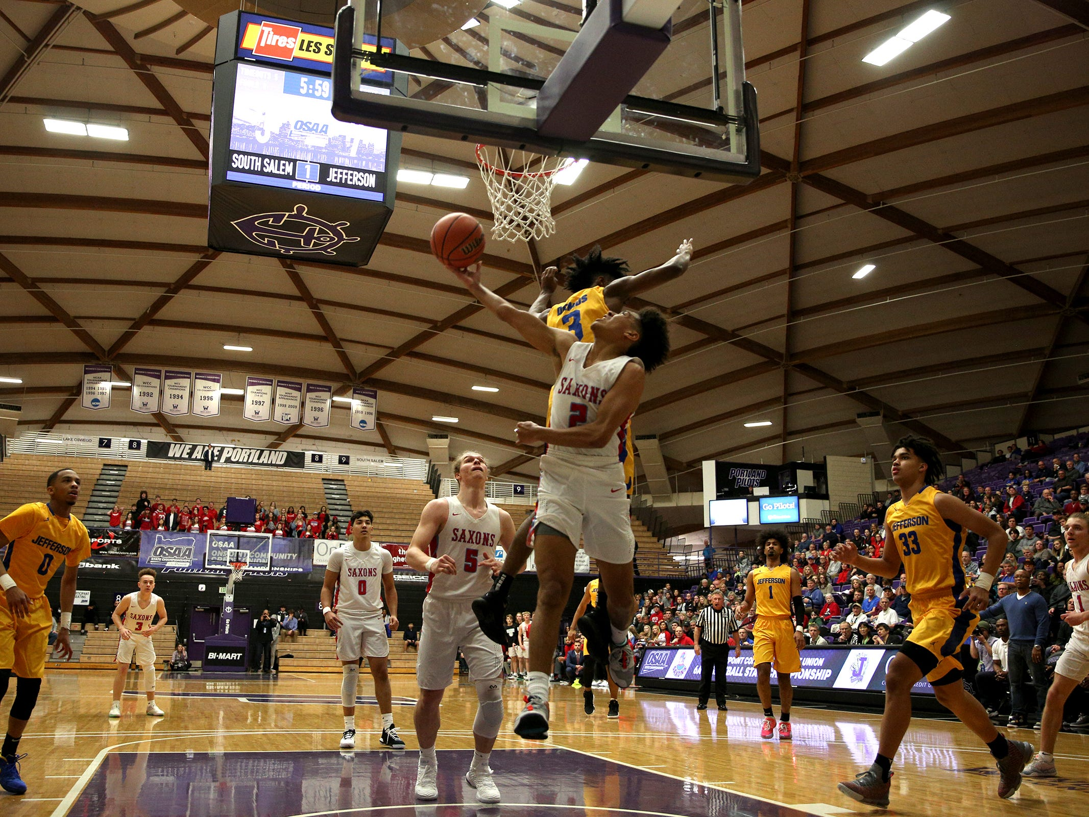 South Salem's Jaden Nielsen-Skinner (2) attempts to get a shot in during the South Salem vs. Jefferson boys basketball OSAA 6A semifinal game at Chiles Center in Portland on Friday, March 8, 2019.