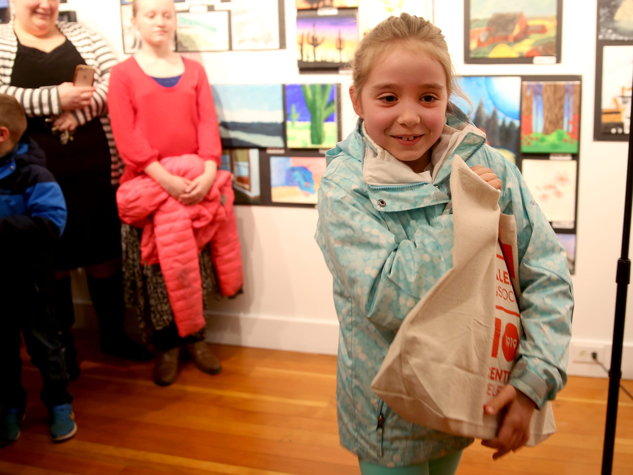Isla Allen, a second-grader from Keizer, accepts the second-place award for elementary students during the 10th annual Young Artists' Showcase at the Bush Barn Art Center in Salem on March 9, 2019. The exhibit features artwork by more than 400 students in Marion, Polk and Yamhill counties and runs through April 20.