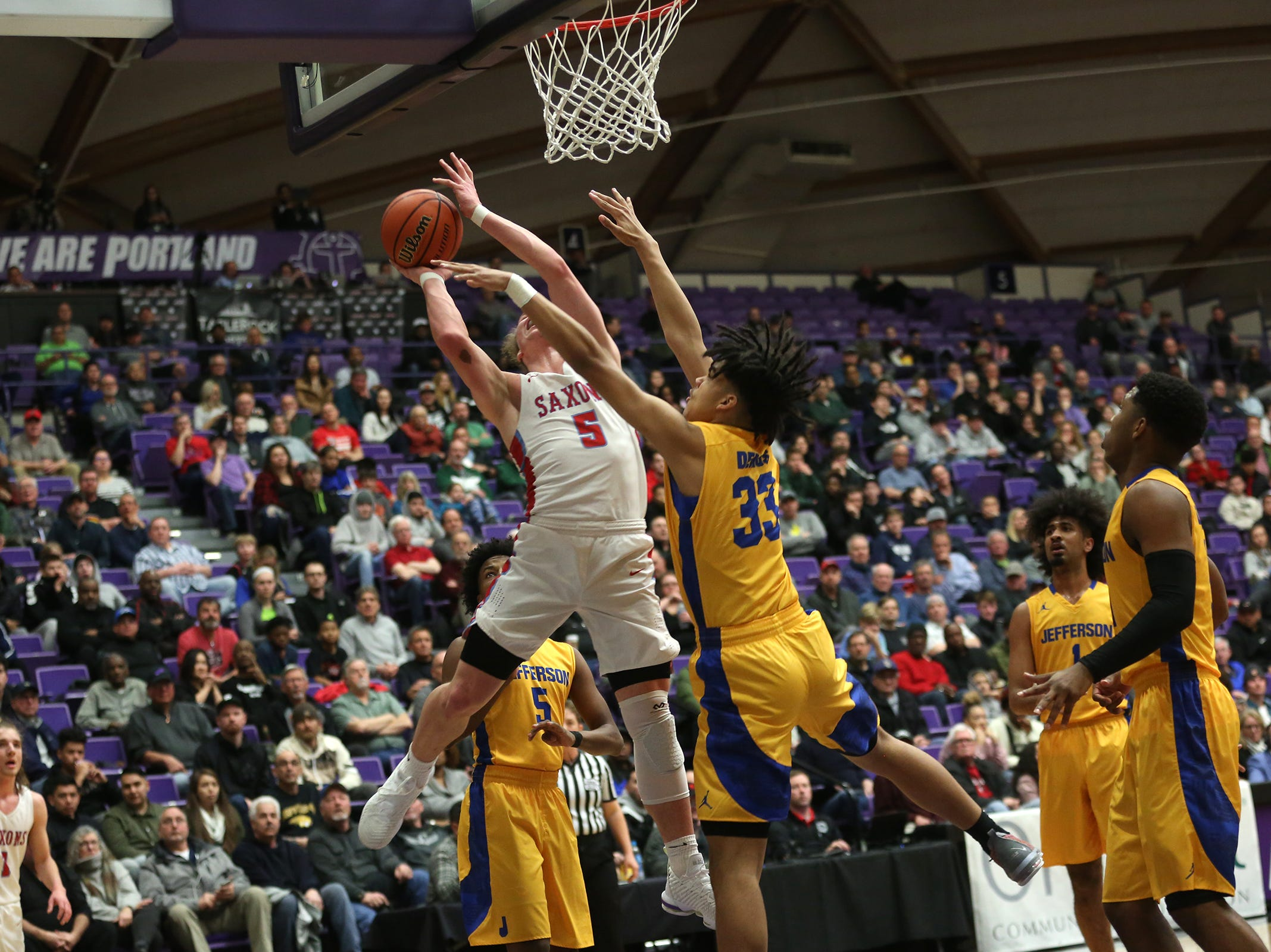 Jefferson's Kamron Robinson (33) is fouled as South Salem's Ryan Brown (5) gets a shot in during the South Salem vs. Jefferson boys basketball OSAA 6A semifinal game at Chiles Center in Portland on Friday, March 8, 2019.