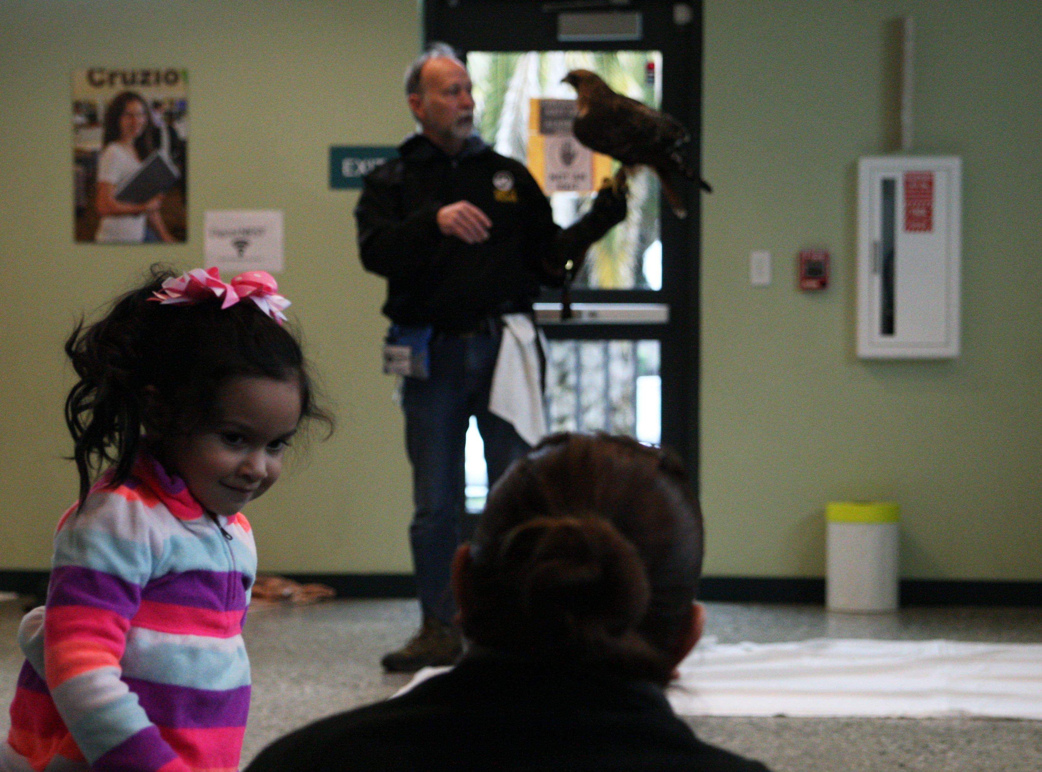 A young girl smiles at her mother during Saturday's presentation on Red-tailed Hawks, featuring a real Red-tailed Hawk.