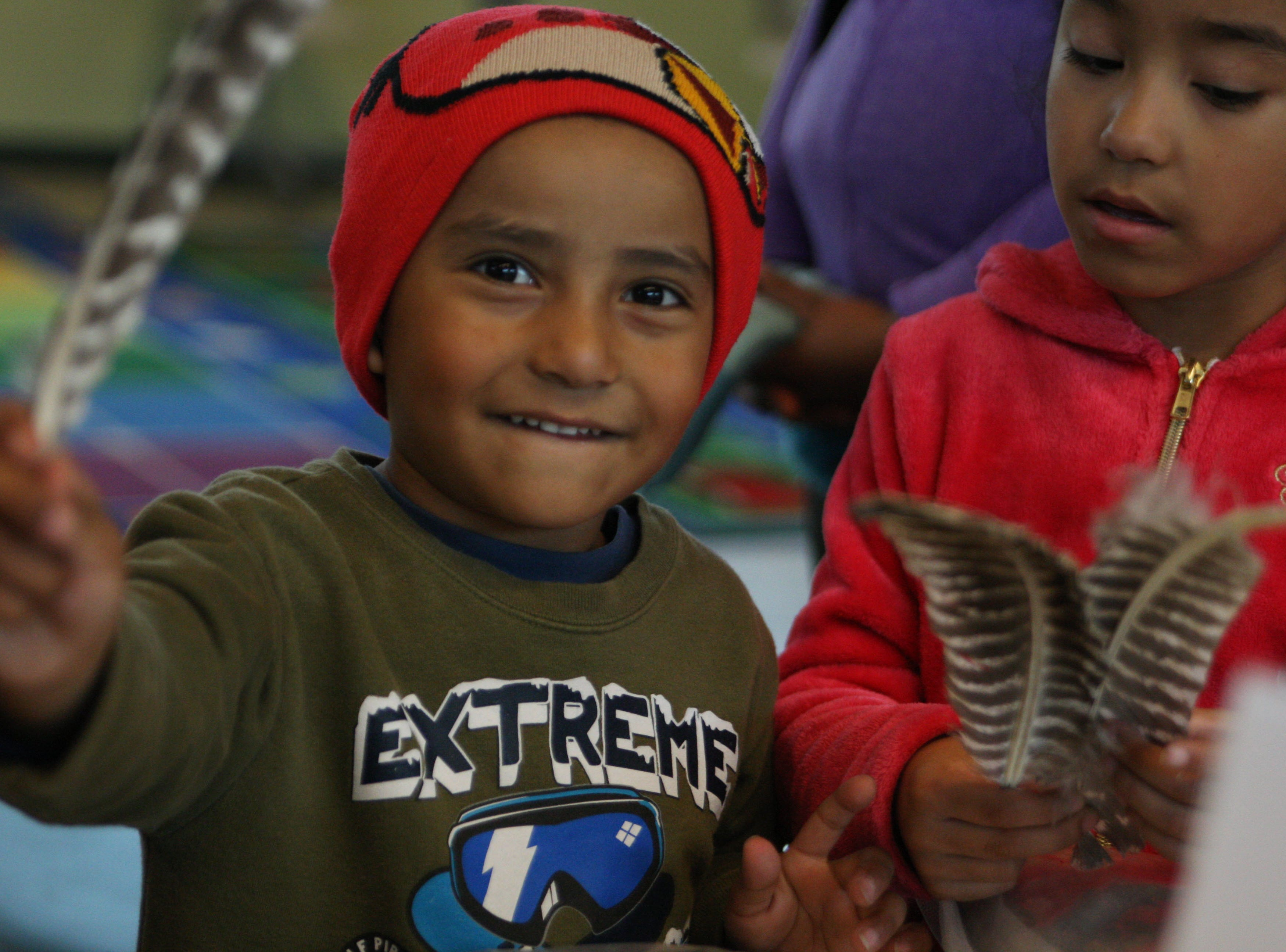 One boy waves a sample feather from a Red-tailed Hawk at Cesar Chavez Library Saturday.