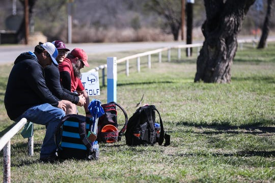 Players sit on the fence while they wait for the next hole to clear during the Crush on the Concho tournament Saturday, March 9, 2019, at Middle Concho Park.