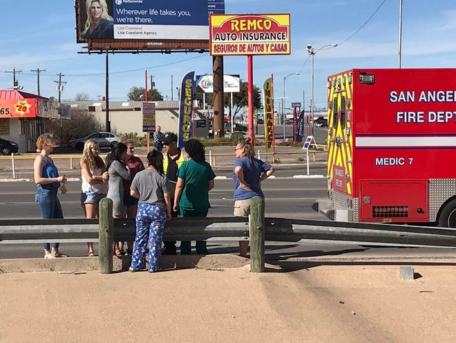 People talk to emergency personnel Saturday, March 9, 2019, on Knickerbocker after a two-vehicle crash.