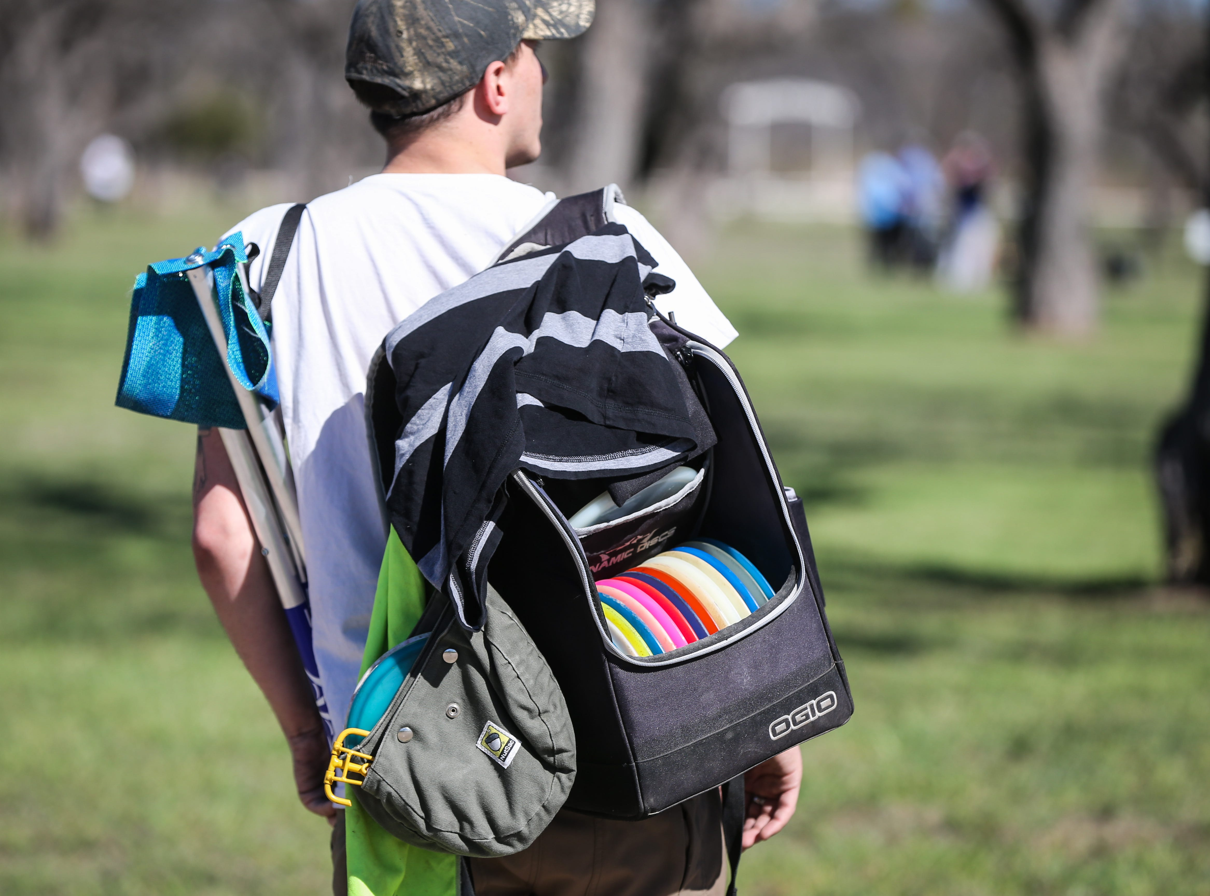 A participant carries his gear to the next hole during the Crush on the Concho tournament Saturday, March 9, 2019, at Middle Concho Park.