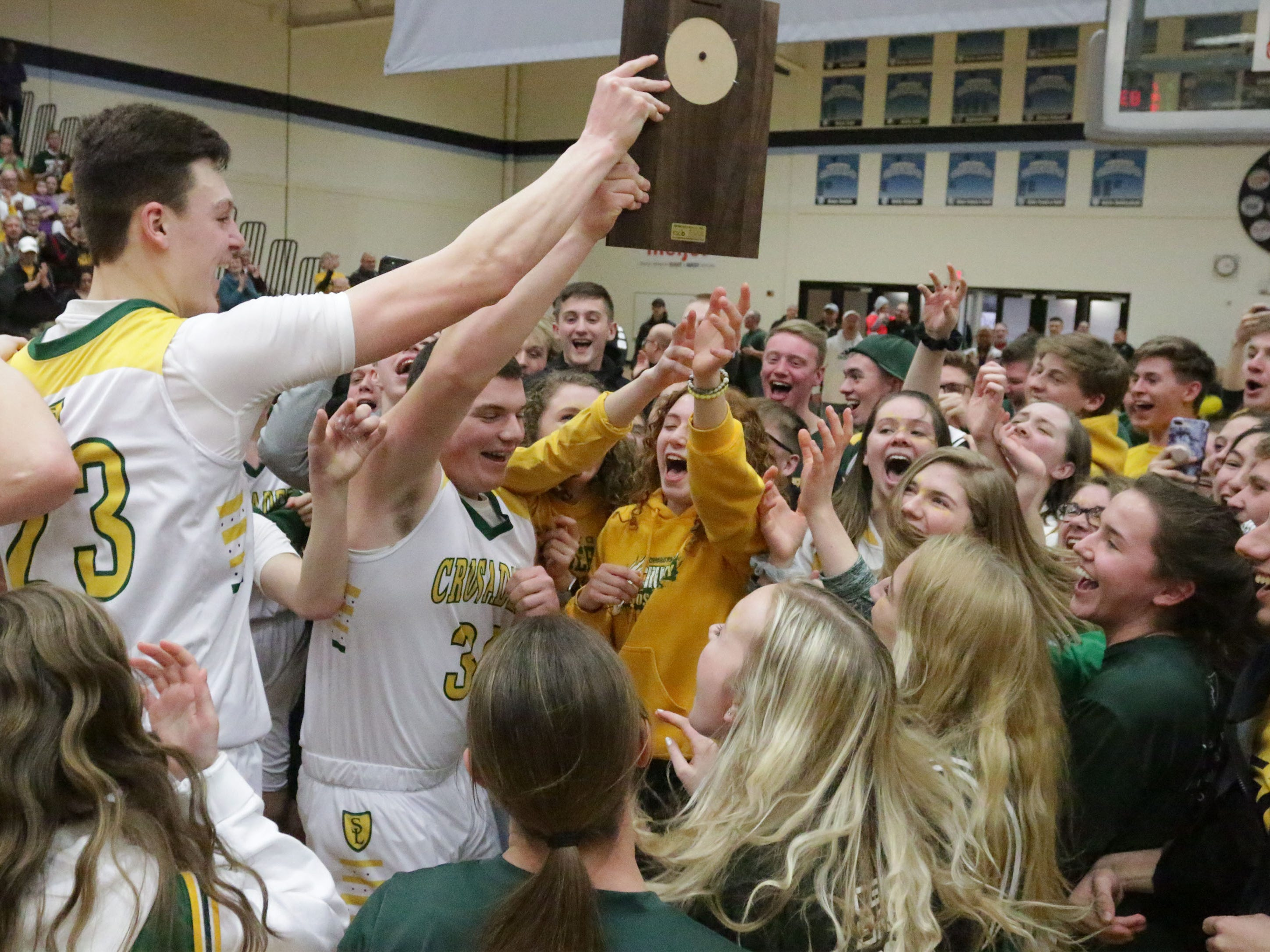 Sheboygan Lutheran players and fans celebrate their 83-69 win over Rio at the WIAA Div. 5 Sectional, Saturday, March 9, 2019, in Sheboygan, Wis.
