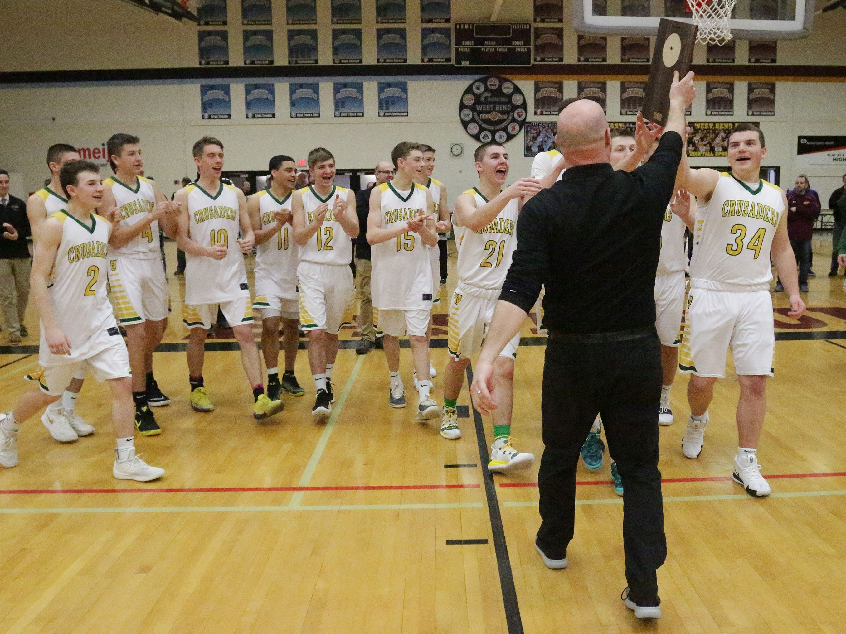 Sheboygan Lutheran coach Nick Verhagen lifts high the WIAA, Div. 5 sectional trophy by his team following their 83-69 win over Rio, Saturday, March 9, 2019, in Sheboygan, Wis.