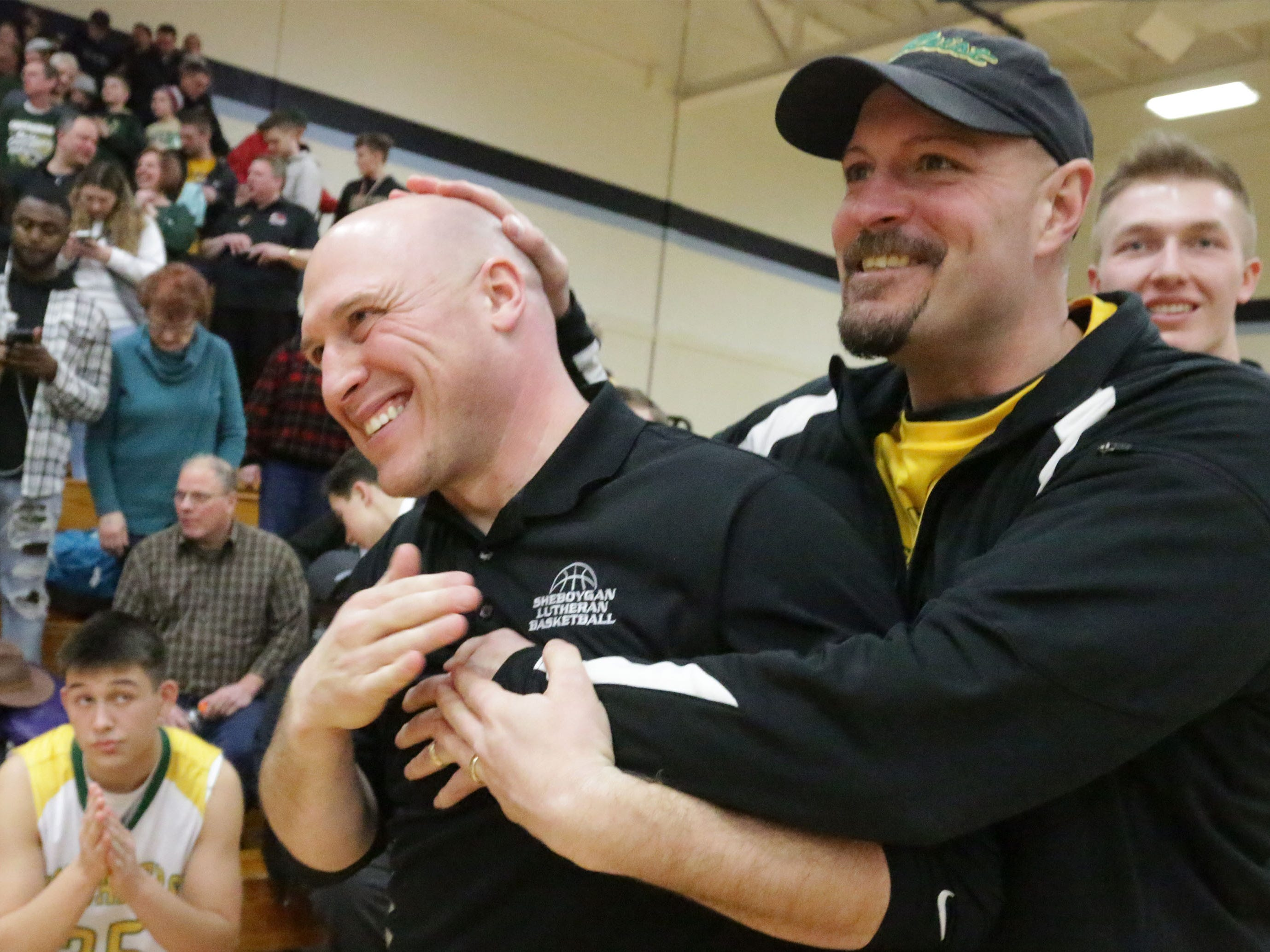 Sheboygan Lutheran Head Coach Nick Verhagen, left, gets a head rub from Brian Ognacevic, right, following the Crusaders' 83-69 win over Rio, Saturday, March 9, 2019, in Sheboygan, Wis. Ognacevic is the father of player Jacob Ognacevic (23).