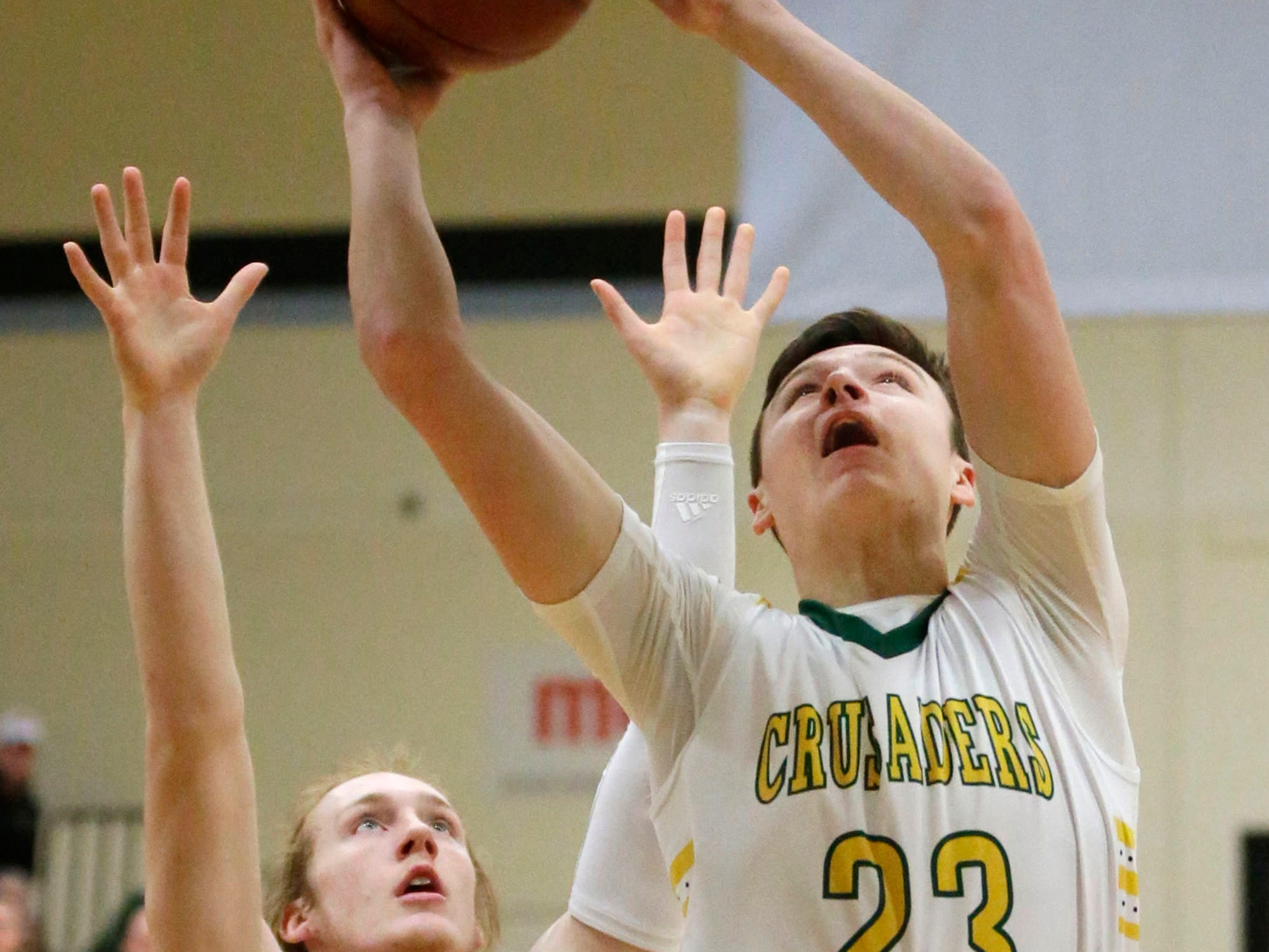 Sheboygan Lutheran's Jacob Ognacevic (23) aims a shot by Rio's Nathan Rippl (24), Saturday, March 9, 2019, in West Bend, Wis.