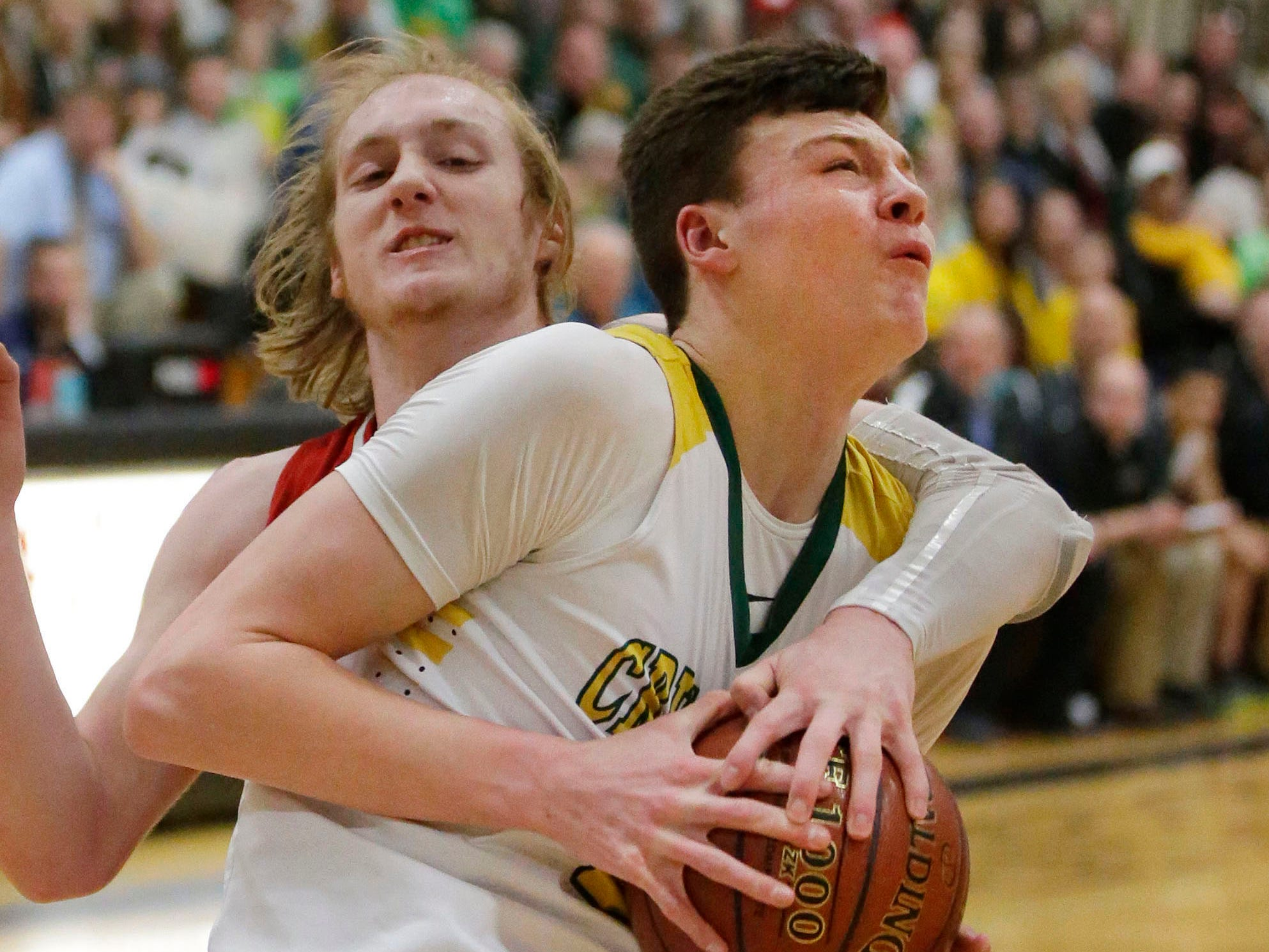 Sheboygan Lutheran's Jacob Ognacevic (23) grips the ball as Rio's Nathan Rippl (24) tries to pry the ball from him, Saturday, March 9, 2019, in West Bend, Wis.