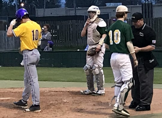 Captain's Shreve's Brandon Smith hands baseballs to an umpire Friday night while Benton's Cade Scott (20) prepares to hit.