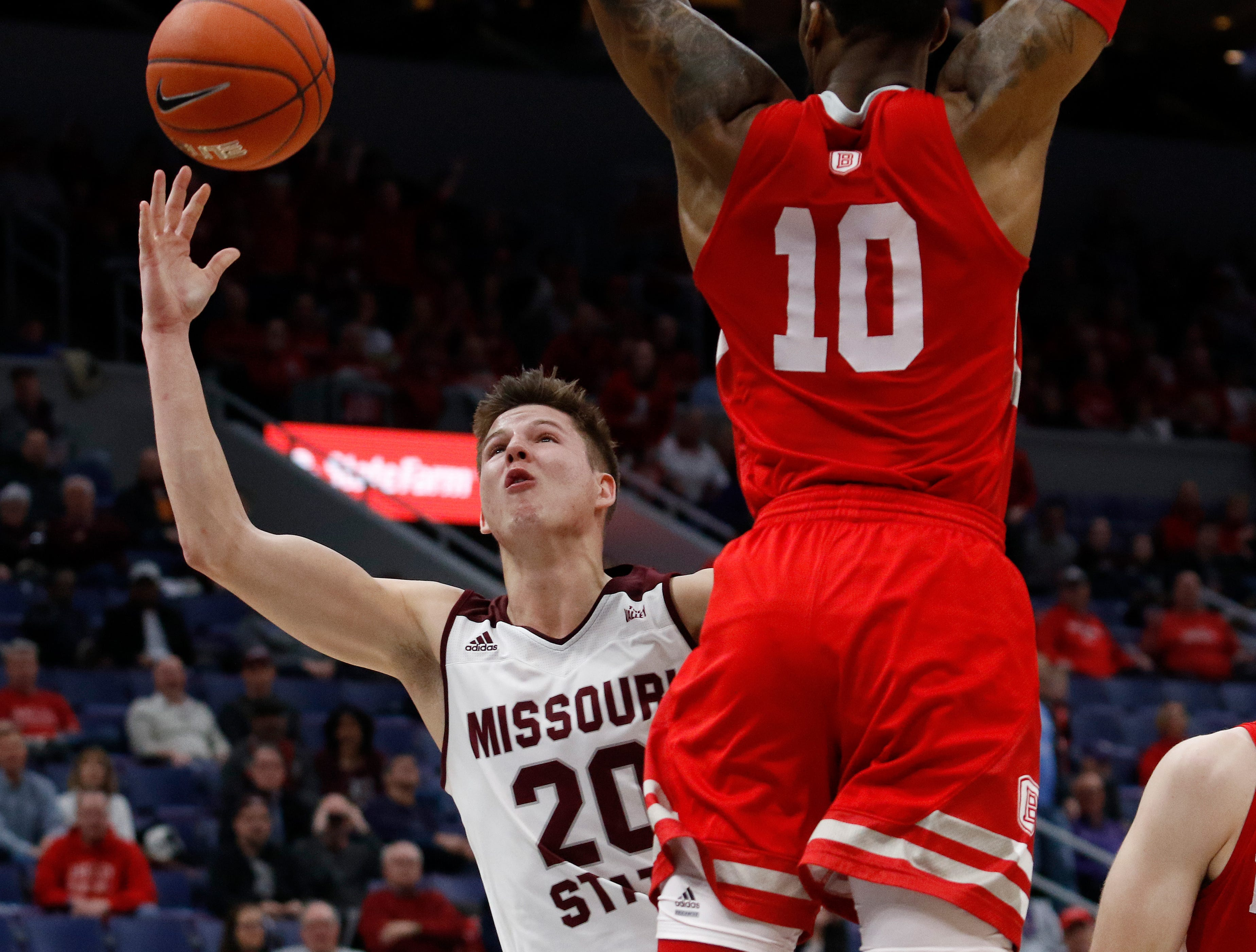 Missouri State's Ryan Kreklow (20) drives the ball defended by Bradley's Elijah Childs (10), Friday, March 8, 2019, at the Enterprise Center in St. Louis.