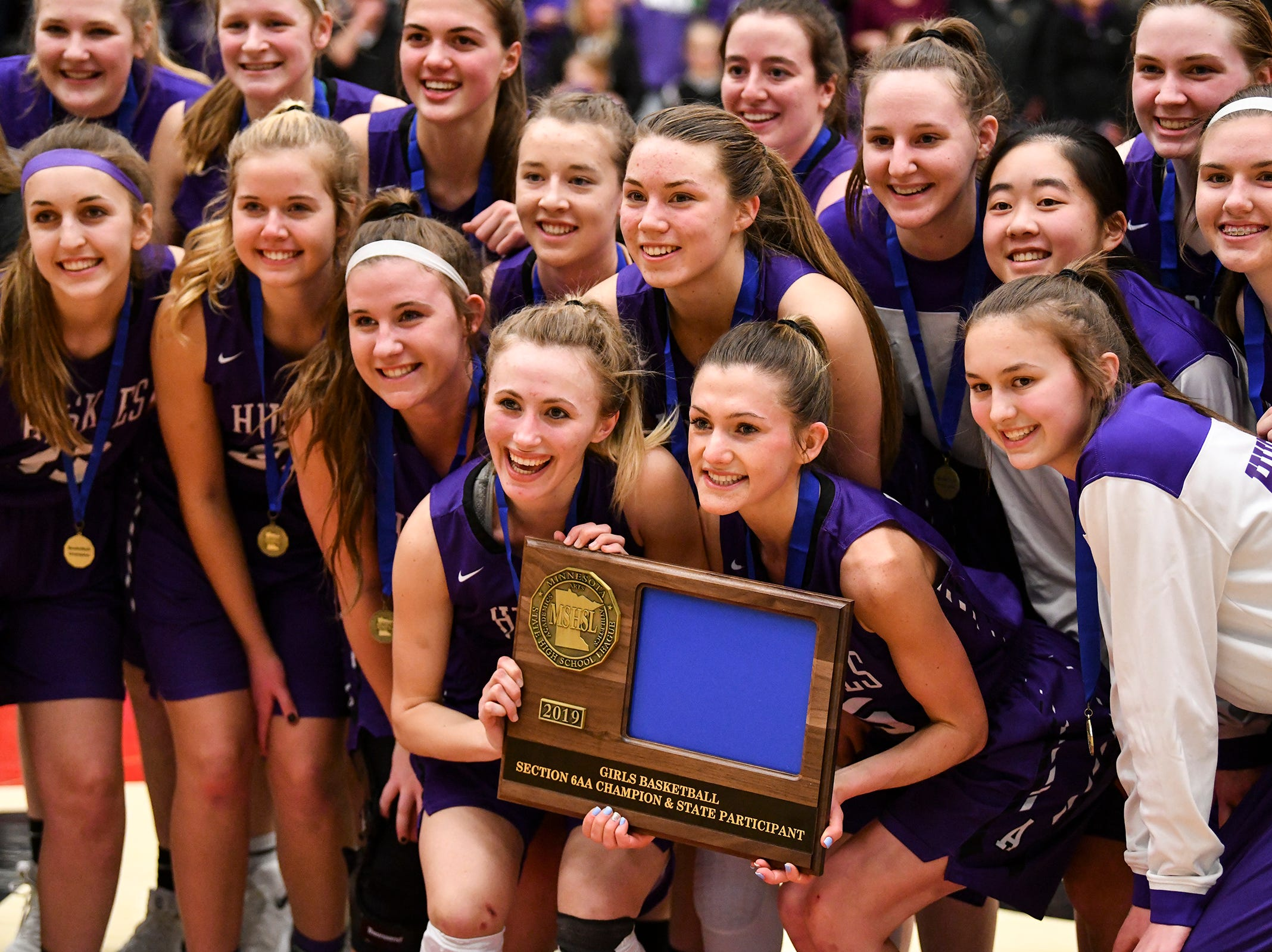 Albany players pose with their section trophy following the Section 6-2A championship game against Pine City Friday, March 8, at Halenbeck Hall in St. Cloud. Albany won 60-29.