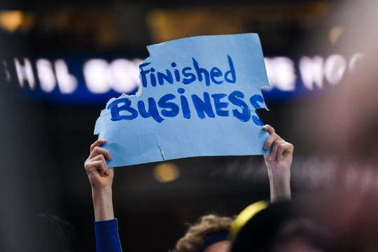 """A Cathedral fan holds a sign with the """"un"""" torn off following the state Class A championship game Saturday, March 9, 2019, at the Xcel Energy Center in St. Paul."""