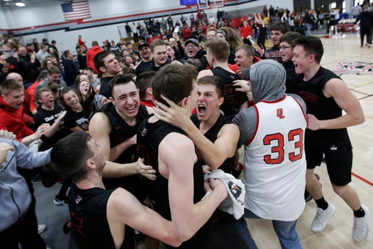 Lourdes Academy's Ben Huizenga (left), Hayden Jones (center) and Caden Chier (right) celebrate after a Division 4 sectional final victory against Marathon on Saturday at Neillsville High School. Jones blocked a 3-pointer at the buzzer to preserve a 72-71 victory.