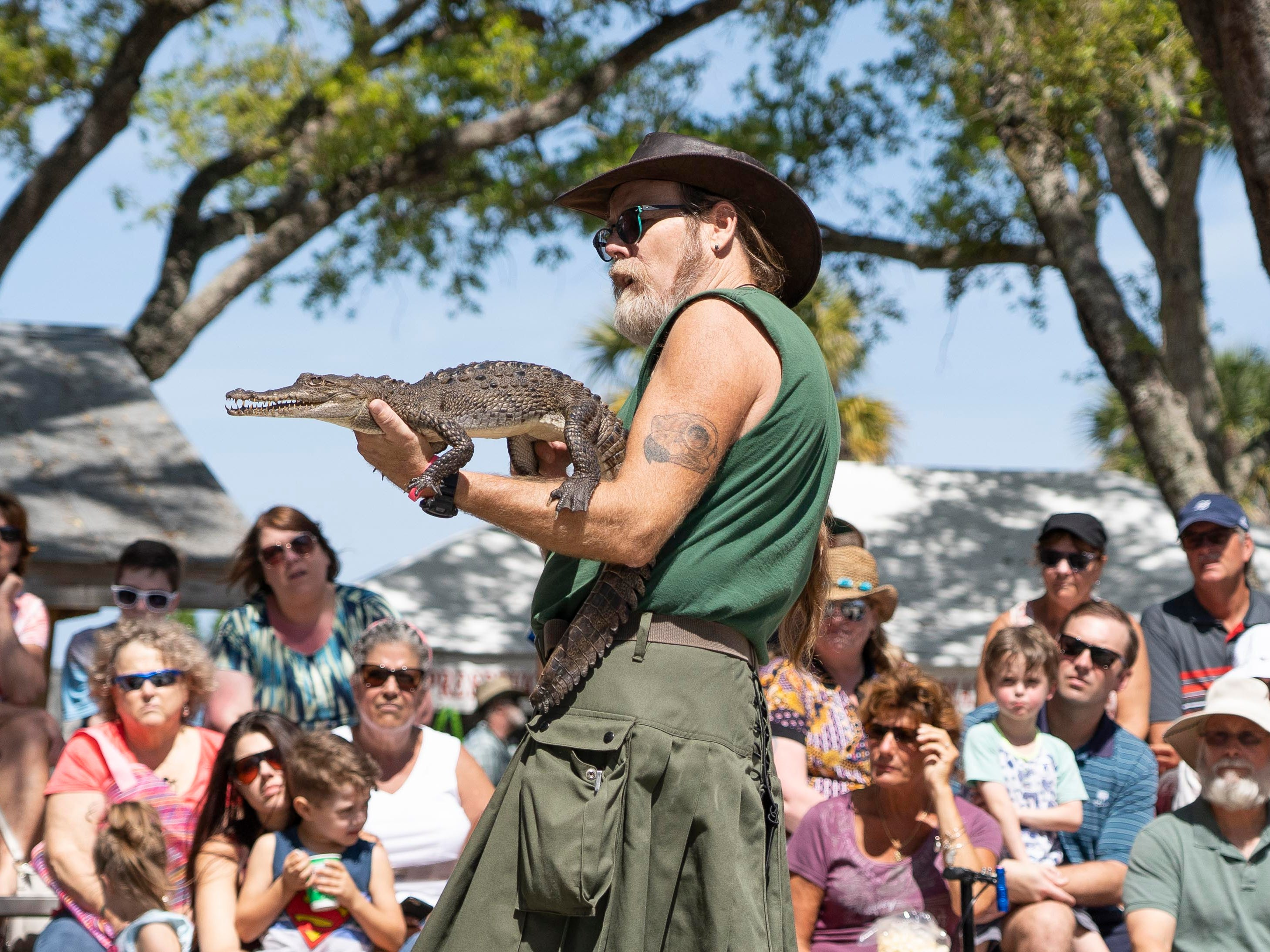 """The animals that we bring are ones that cannot be released back into the wild, but they can be ambassadors for their wild cousins. Most people don't get close to wild animals anymore, so we take the animals to the people,"" said Tim Brown, center, Director of Education at the Treasure Coast Wildlife Center in Palm City, who talks about an American crocodile to the crowd at the 27th annual Pelican Island Wildlife Festival on Saturday, March 9, 2019, at Riverview Park in Sebastian. The festival celebrates the anniversary of the establishment of Pelican Island as the nationÕs first national wildlife refuge on March 14, 1903, by President Theodore Roosevelt."