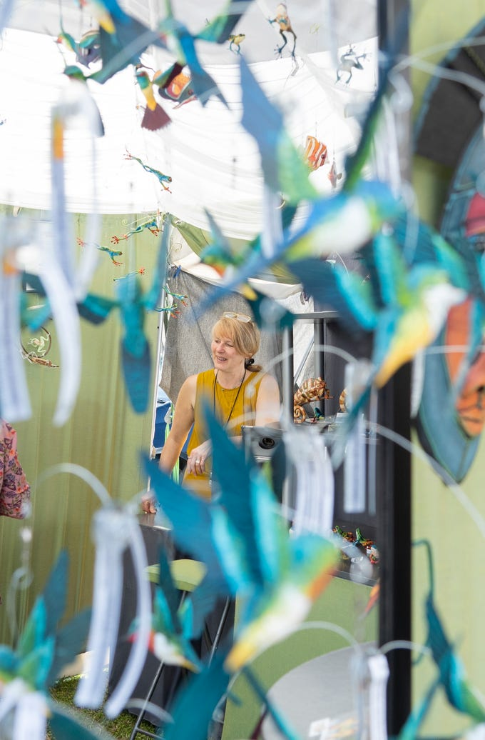 """When I was little I was always doing something creative.  We were always outside picking up bugs and frogs,"" said Mary Hager of Adell, Wisconsin, who is reflected in a mirror as she talks to a customer in her booth at the 68th annual Under the Oaks Fine Arts & Crafts Show on Saturday, March 9, 2019, in Riverside Park in Vero Beach. Hager is a 3D mixed media artist whose pieces are inspired by nature. The event is the largest fundraiser of the Vero Beach Art Club. More than 220 artists from around the nation and beyond exhibited at the juried show. Sunday hours are from 10 a.m. to 4 p.m."