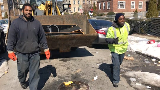 Mount Vernon DPW workers Hector Ruiz (right) and Jeffrey Willims (left) load trash into a front-end loader