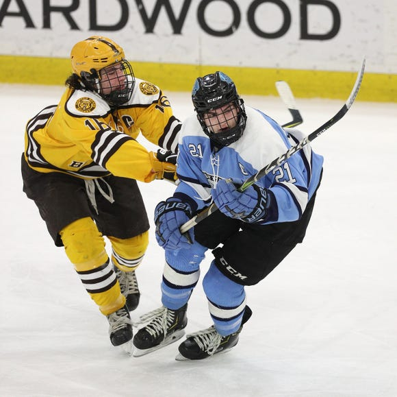 Suffern's Kyle Foresta chips the puck away from Canton's Antonio Vecchio.