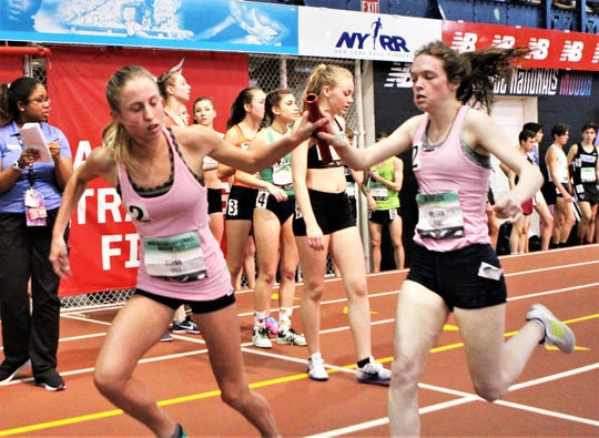 Lily Flynn takes baton from Ursuline teammate Haley McLean en route to winning the 2019 girls 4xmile national championship relay.
