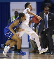 Sanford's Corey Perkins takes the ball up court as he is pursued by Dover's Wanya Wise in the first half of the Warriors' 48-45 win in the DIAA state championship Saturday at the Bob Carpenter Center.