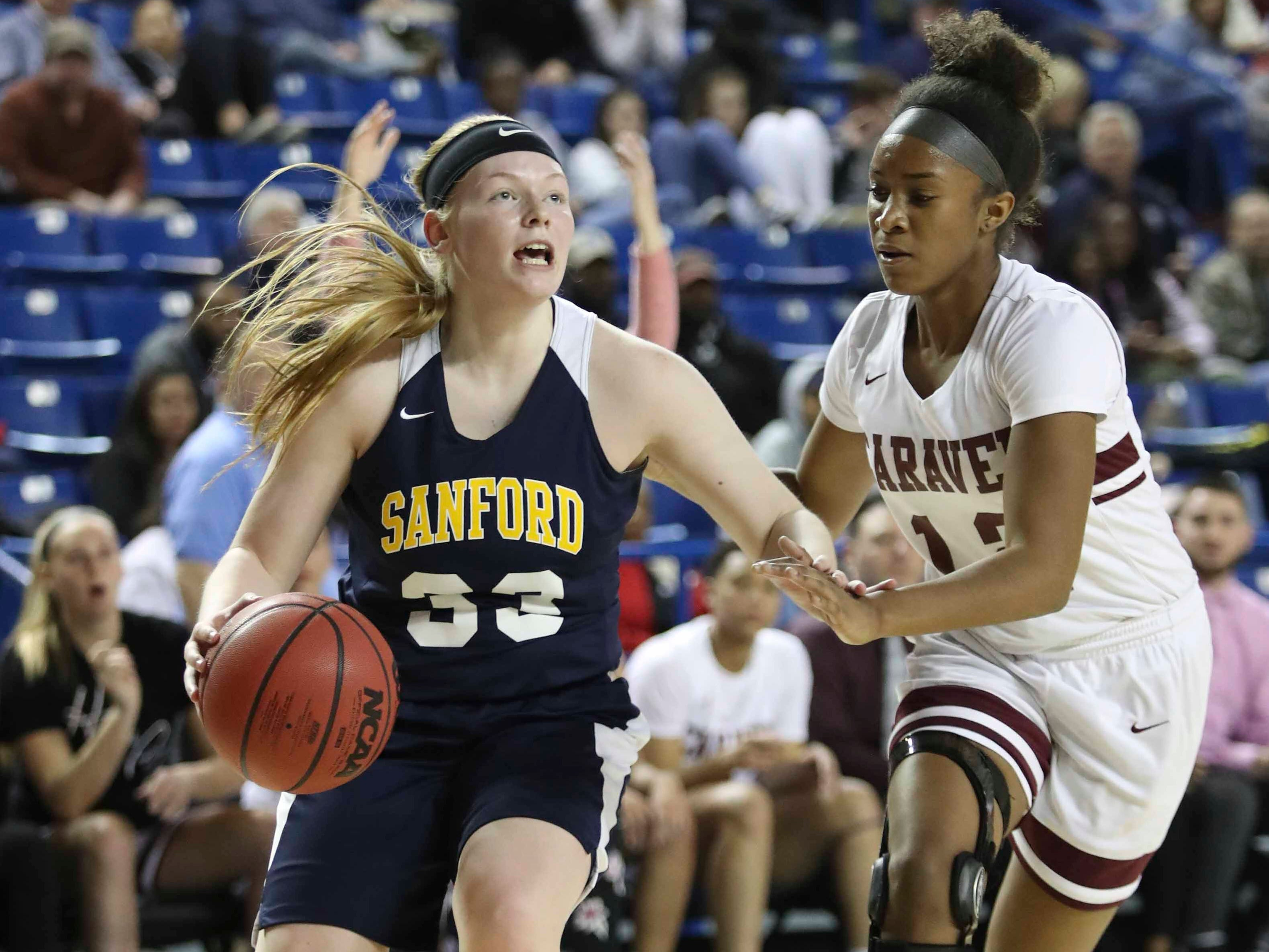 Sanford's Olivia Tucker (left) moves against Caravel's Taylor Wilkins in the first half of the DIAA state tournament championship game at the Bob Carpenter Center Friday.