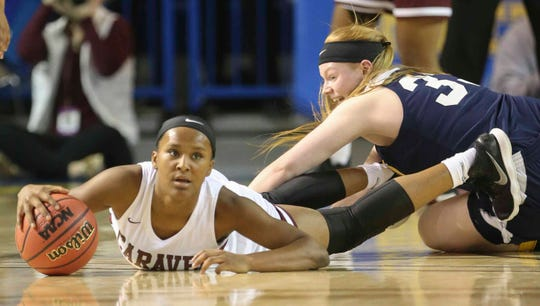 Caravel's Sasha Marvel (left) grabs a loose ball in front of Sanford's Olivia Tucker in the first half of the DIAA Girls Basketball Tournament championship game at the Bob Carpenter Center Friday.
