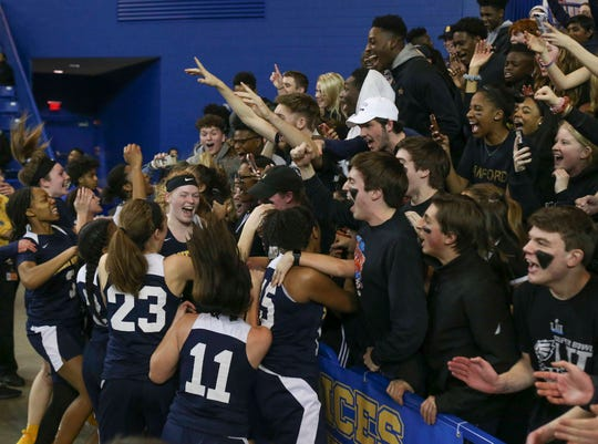 The Sanford girls basketball team joins the student section in celebrating its title after winning the DIAA Girls Basketball Tournament championship game with a last-second shot against Caravel, 51-49,  at the Bob Carpenter Center Friday.