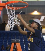 Sanford's Lauren Park gets her piece of the net after the Warriors' 51-49 win in the DIAA Girls Basketball Tournament championship game at the Bob Carpenter Center on March 8.
