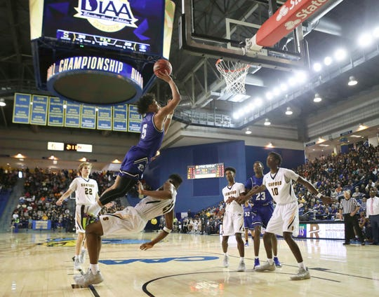 Sanford's Nnanna Njoku draws an offensive foul on Dover's Elijah Allen in the second half of the Warriors 48-45 win in the DIAA state championship Saturday at the Bob Carpenter Center.