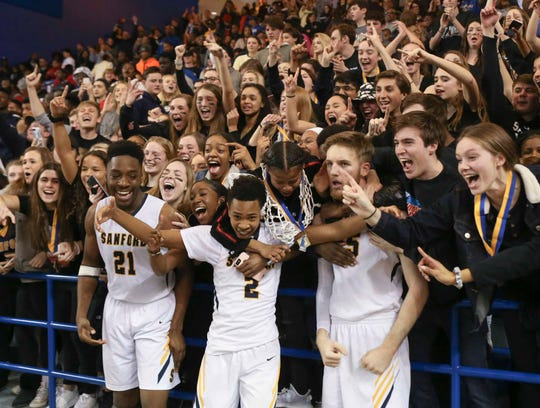 Sanford's (from left) Nnanna Njoku, Corey Perkins and Ryan McKeon visit the student section, including the girls title winning team, after the Warriors' 48-45 win in the DIAA state championship Saturday at the Bob Carpenter Center.