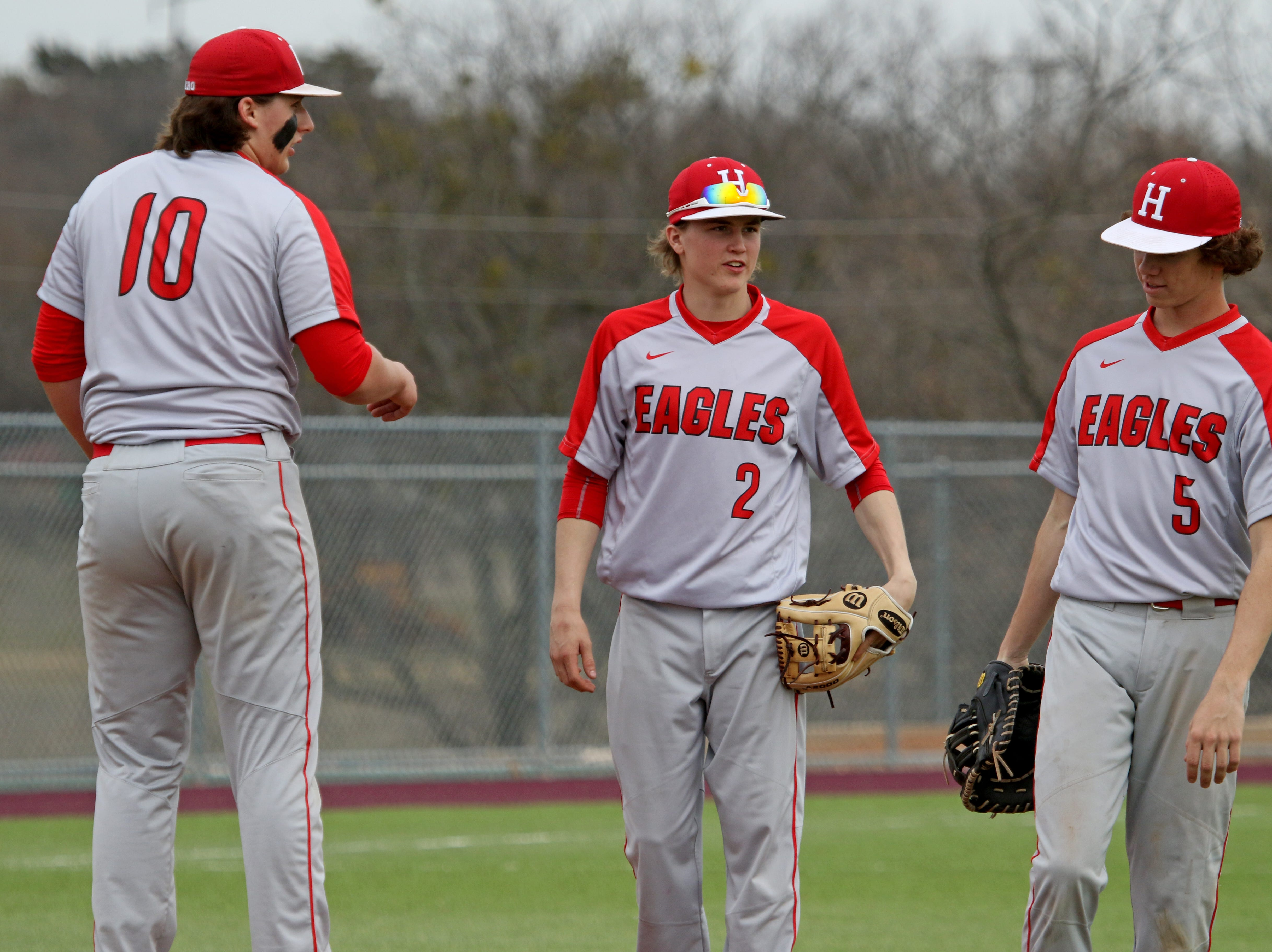 Holliday's Blake Lindemann, left, Hadley Harrigal and Garrison Hall talk on the mound in the game against Wichita Falls High School Friday, March 8, 2019, in Bowie for the Walker Stallcup Tournament.