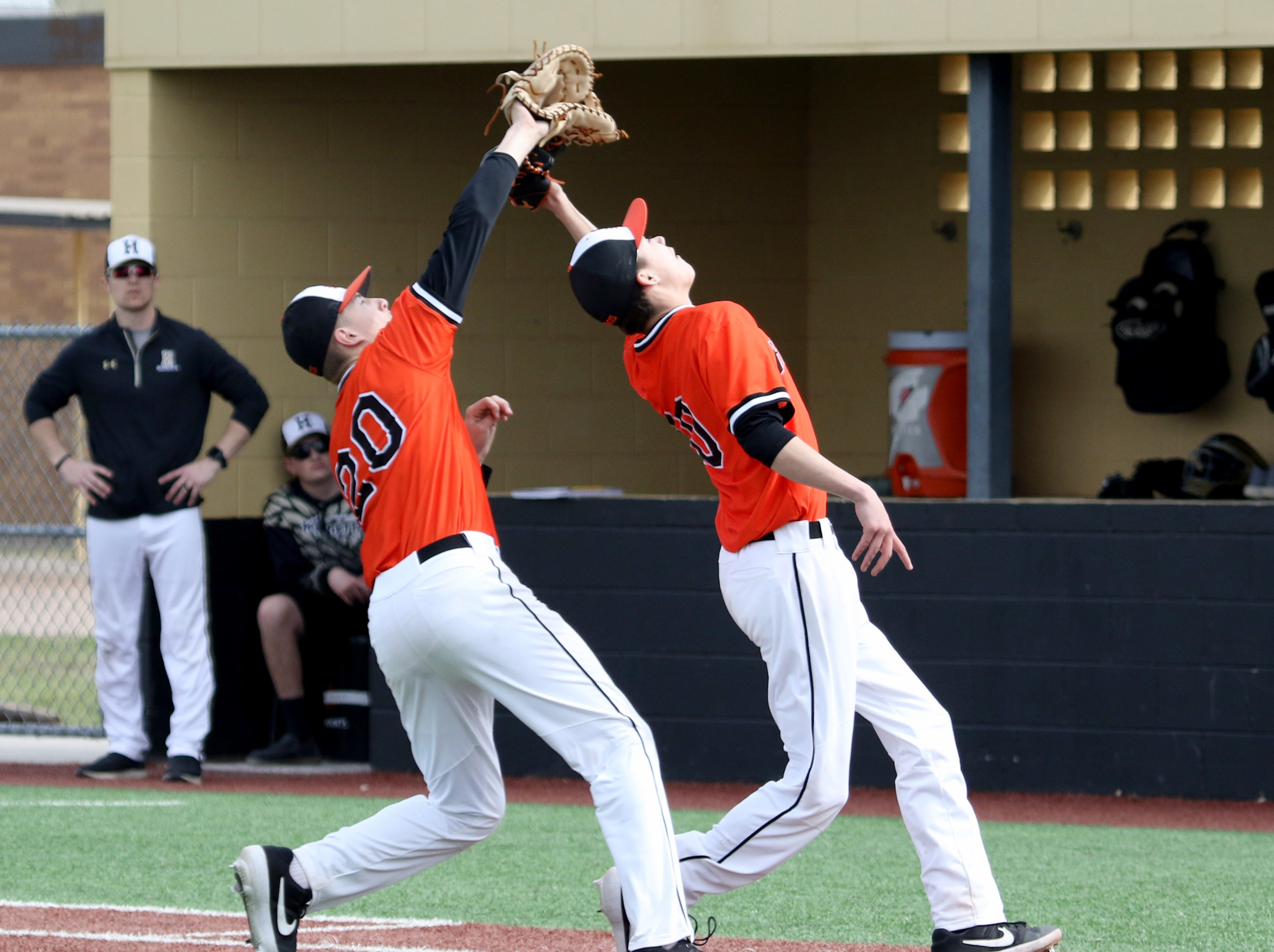Burkburnett's Caleb Mooney, left, catches the pop-up over Andrew Hawkins in the game against Henrietta Friday, March 8 , 2019, in Henrietta.