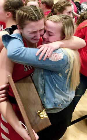 Sheridan senior Jenna Montgomery holds the regional championship trophy while getting a hug from former teammate Sara Cooper following the Generals' 48-46 win against New Philadelphia on Friday night at Winland Memorial Gymnasium.
