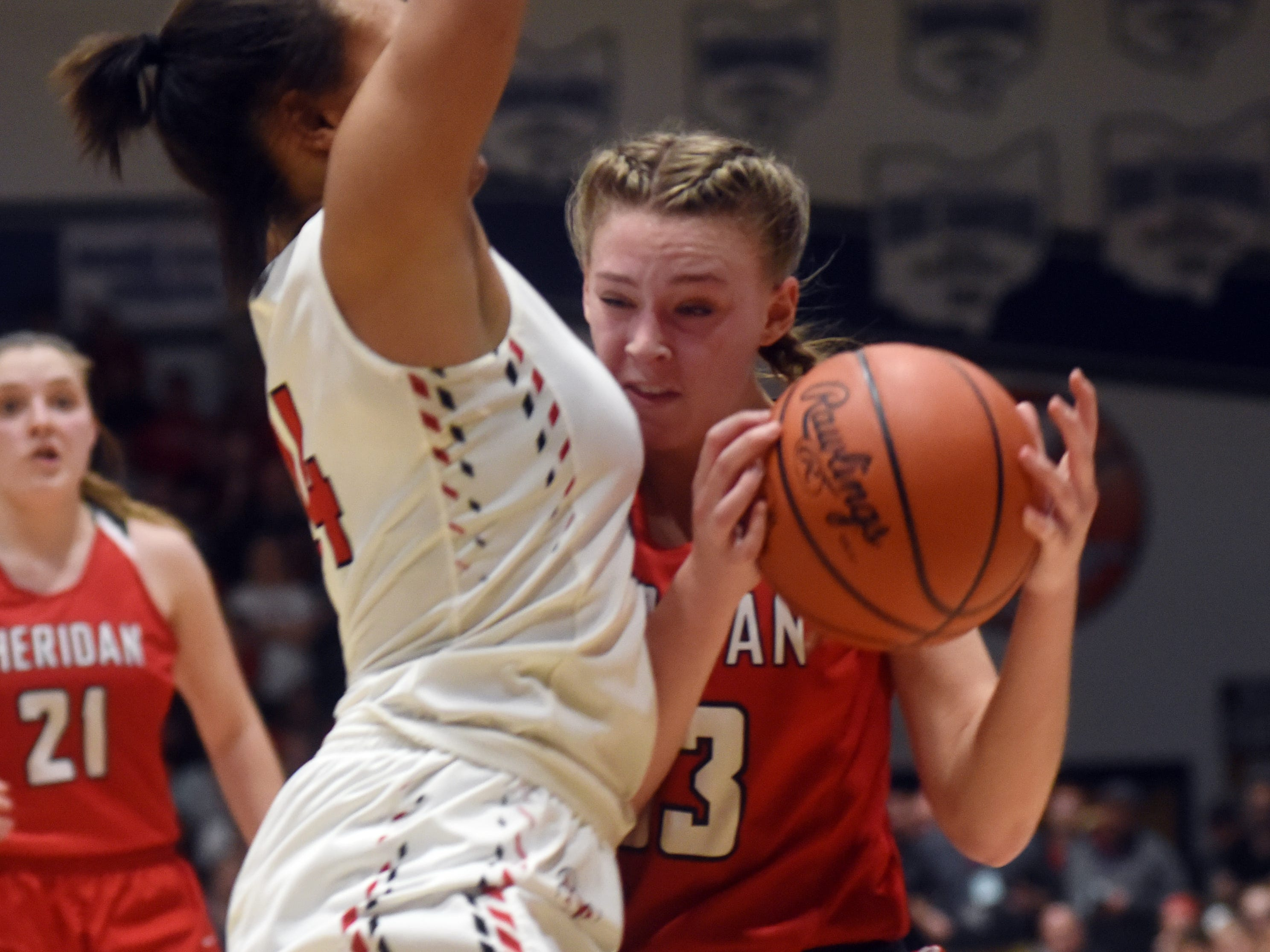 Emma Conrad is met the lane by New Philadelphia's Aaliyah Currence. Sheridan reached its first state tournament since 2004 with a 48-46 win against New Philadelphia on Friday night at Winland Memorial Gymnasium.