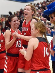 Sheridan celebrates in front of their bench following a 48-46 overtime win against New Philadelphia in a Division II regional final on Friday night at Winland Memorial Gymnasium.