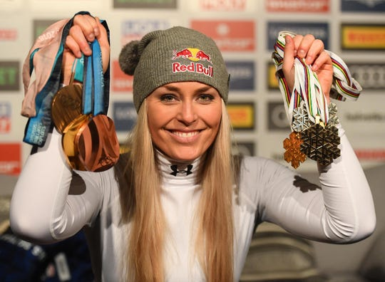Lindsey Vonn holds up medals won during her career after the downhill alpine skiing race at the world shampionships in Sweden.