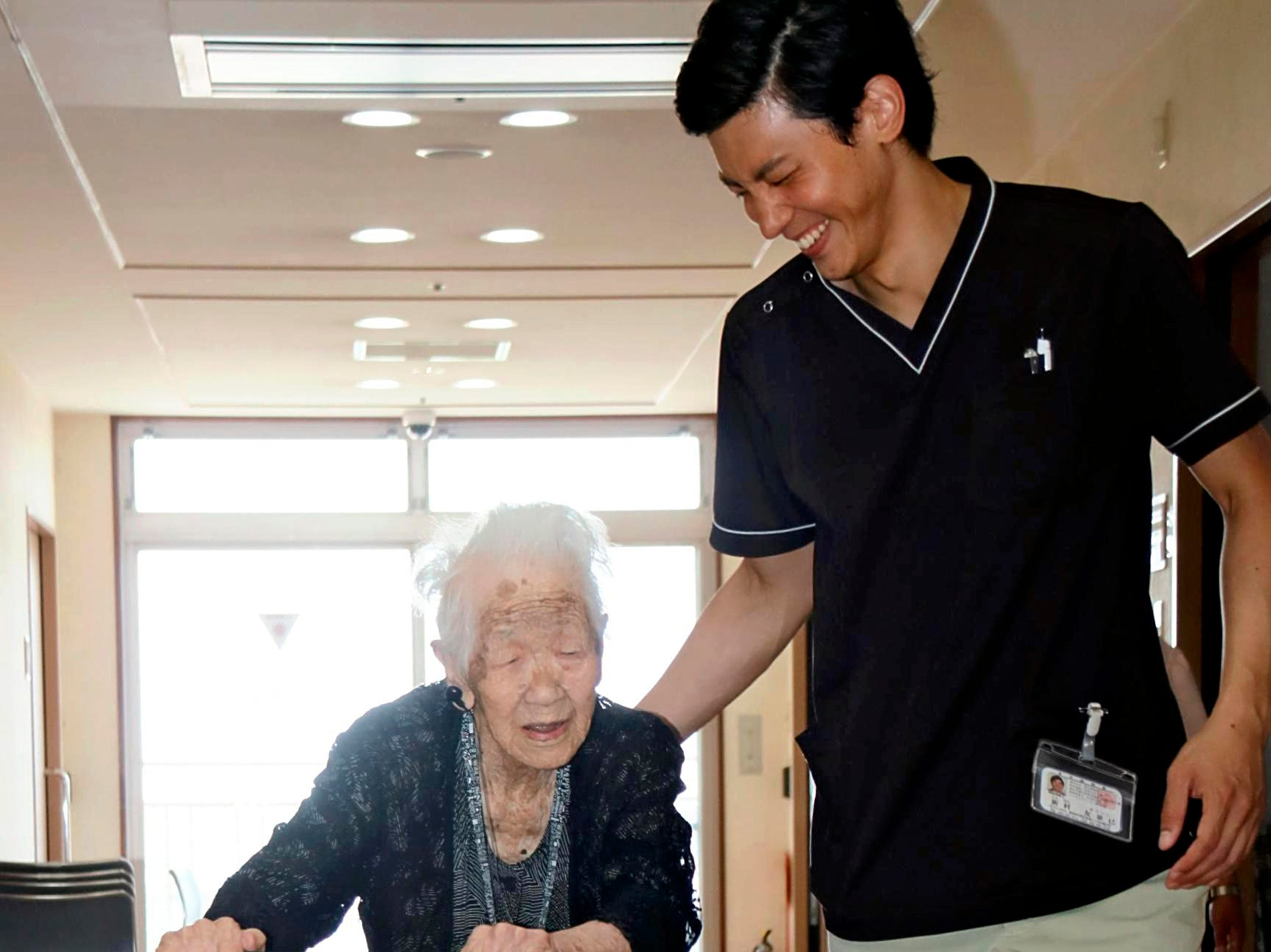 Kane Tanaka, Japan's oldest person, walks using a walker at a nursing home in Fukuoka on July 27, 2018. 115-year-old Tanaka spoke to media on the same day that she thanks everyone around her to live long. Tanaka was born in Fukuoka in 1903, married a rice shop owner and is blessed with children, grandchildren and great-grandchildren.