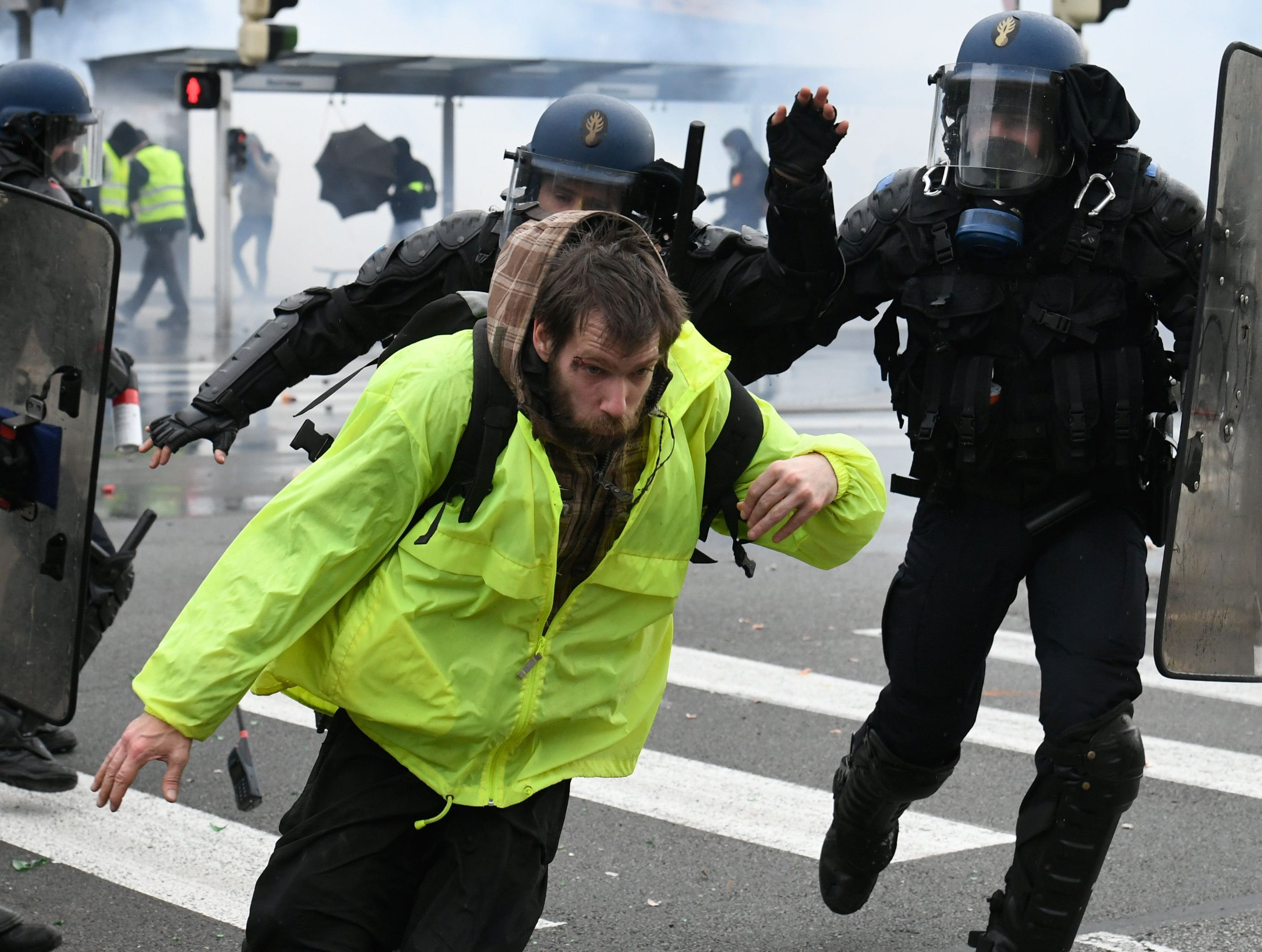"Riot police run after a protester wearing a ""Yellow vests"" (Gilets Jaunes) during a protest on March 9, 2019 in Quimper, western France. Around 800 protestors gathered in Quimper as ""Yellow Vests"" protesters take to the streets in France for the 17th consecutive Saturday."