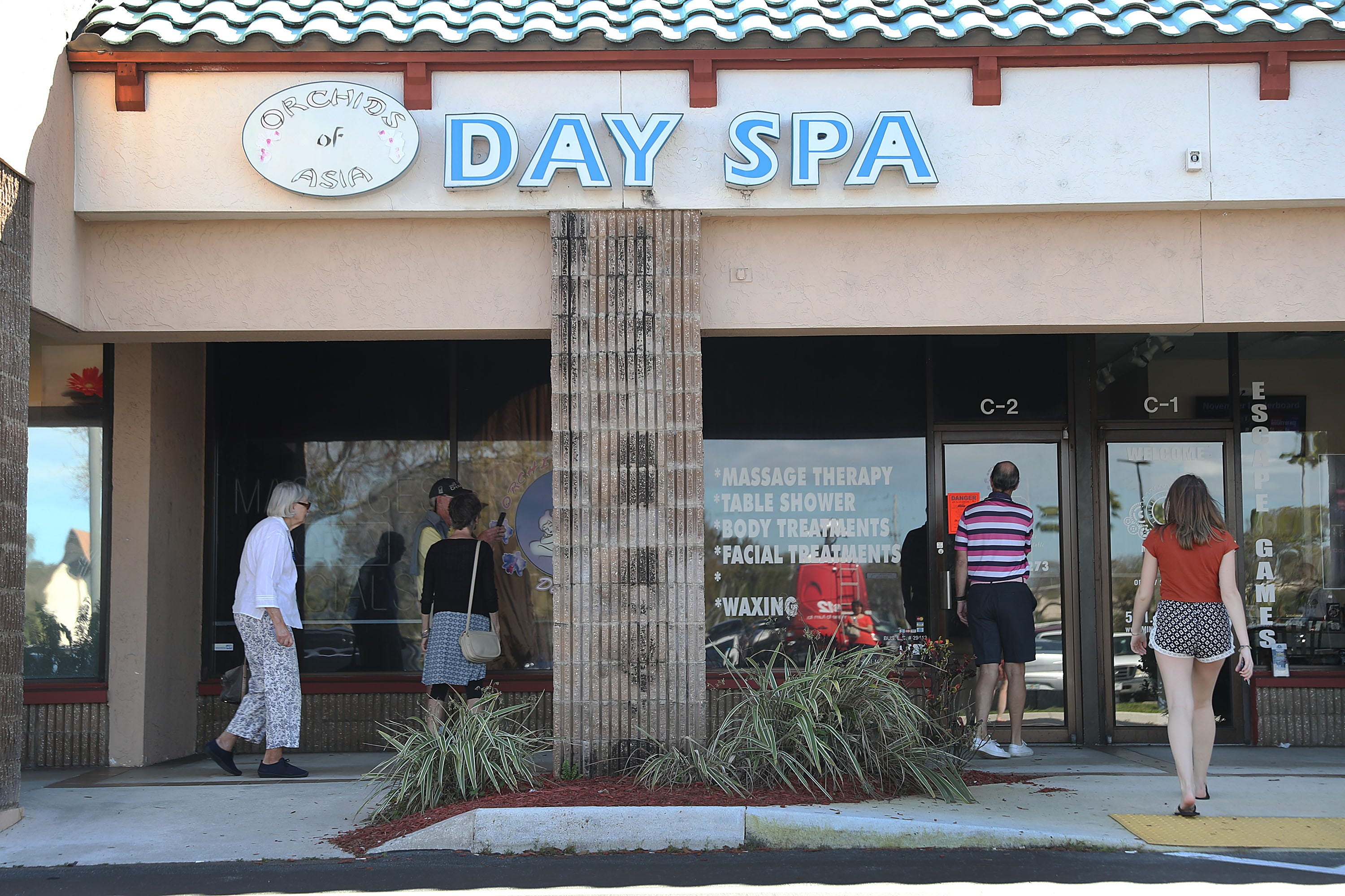 People mill around in front of the Orchids of Asia Day Spa after New England Patriots owner Robert Kraft was charged Feb. 22, 2019, with allegedly soliciting sex in Jupiter, Florida. Kraft was caught up in a law enforcement operation in South Florida that netted hundreds of johns over the past two weeks.