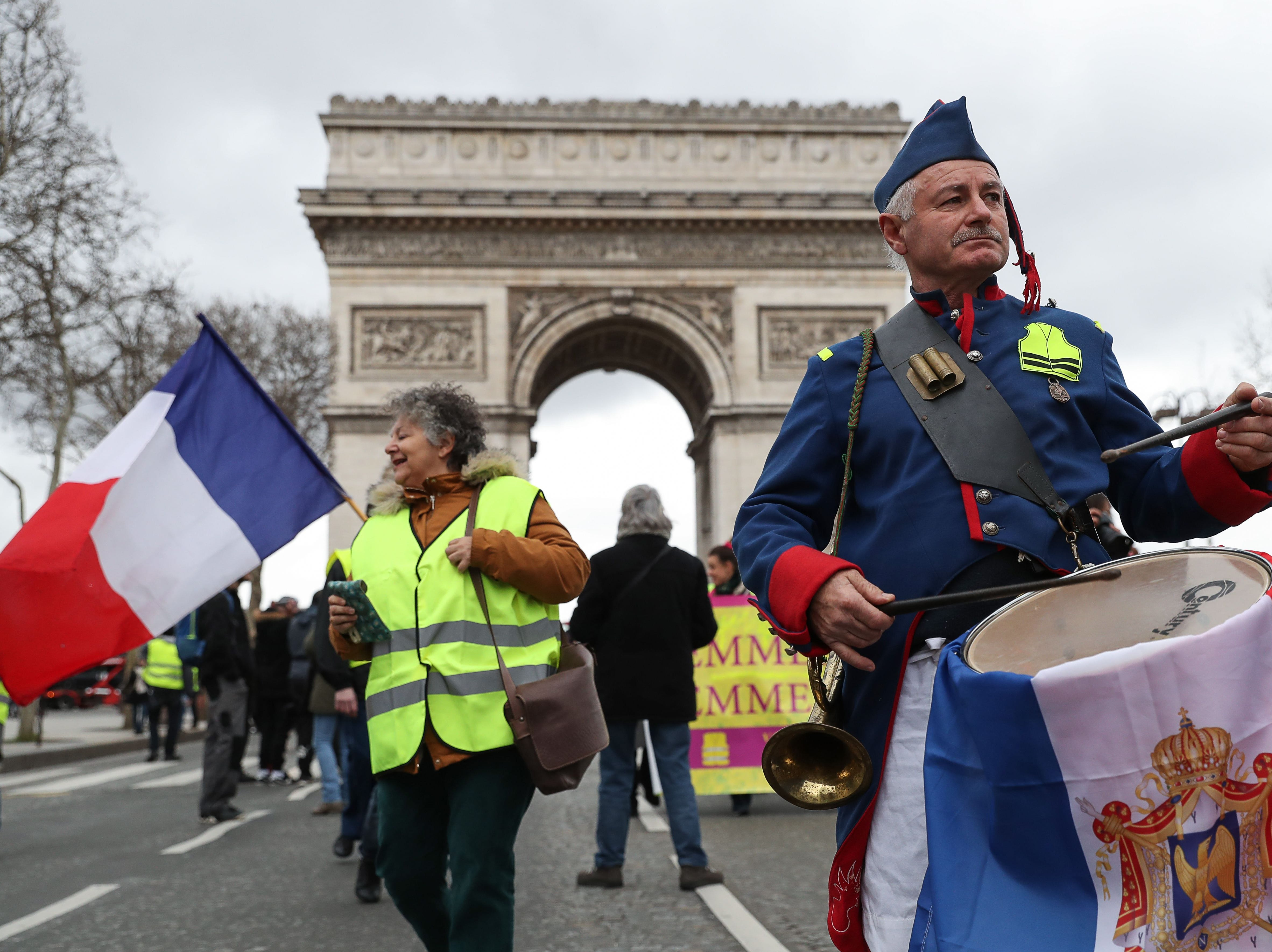 "A ""Yellow Vest"" (Gilet Jaune) protester wearing a uniform inspired by the Napelonic era plays a drum as he takes part in an anti-government demonstration in front of the Arc de triomphe in Paris, on March 9, 2019."